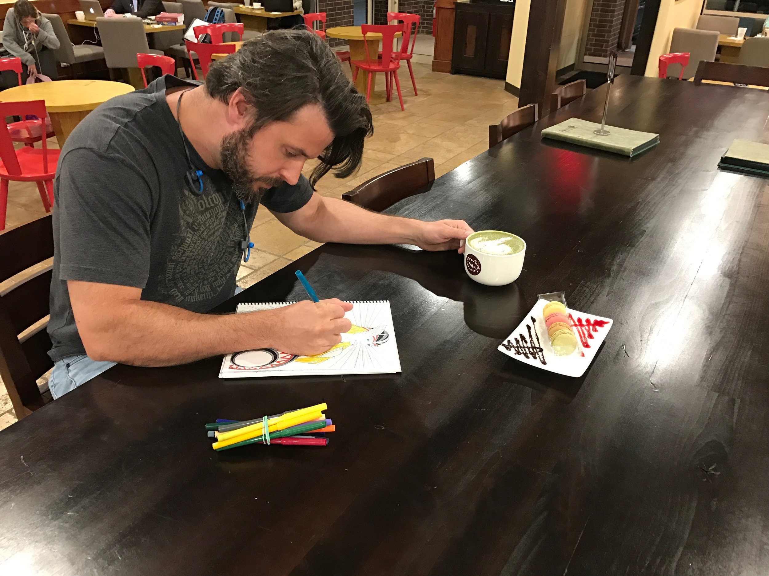 Zach relaxing in a coffee shop coloring  Legends of Norse adult-themed coloring book.