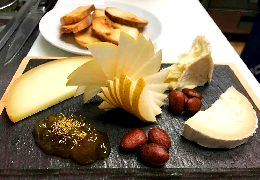 Lou Bird's Cheese Board  featuring St. Stephens Triple Cream, Cana de Cabra, and P'tit Basque cheeses. Accompanied by smoked marcona almonds, sliced pear, fig jam and house crustini.