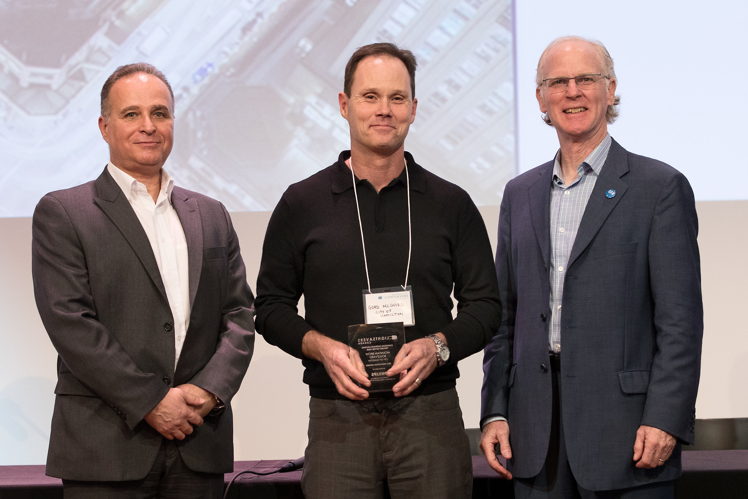 Gord McGuire accepting the award on behalf of the  City of Hamilton  with Peter Halsall of LightSavers and Angelo Miceli of Philips Lighting.