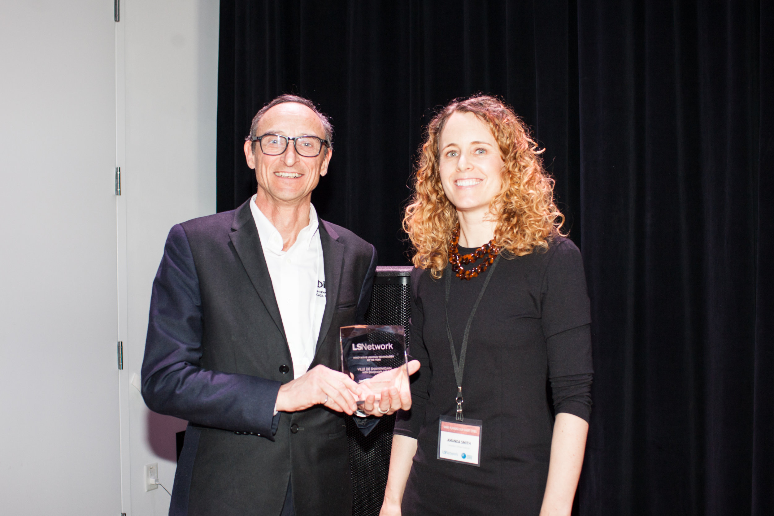 Bernard Tetu, President of DimOnOff, accepting the award on behalf of the City of Shawinigan and DimOnOff, with Amanda Smith of LSNetwork.