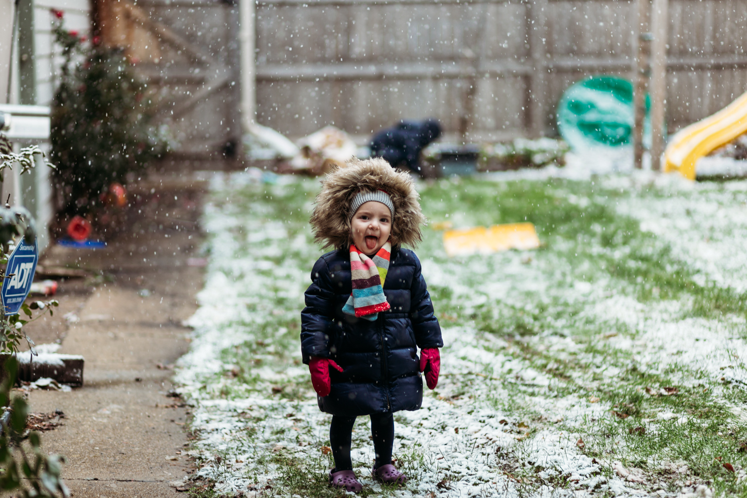 Little girl catching falling snow with her tongue.