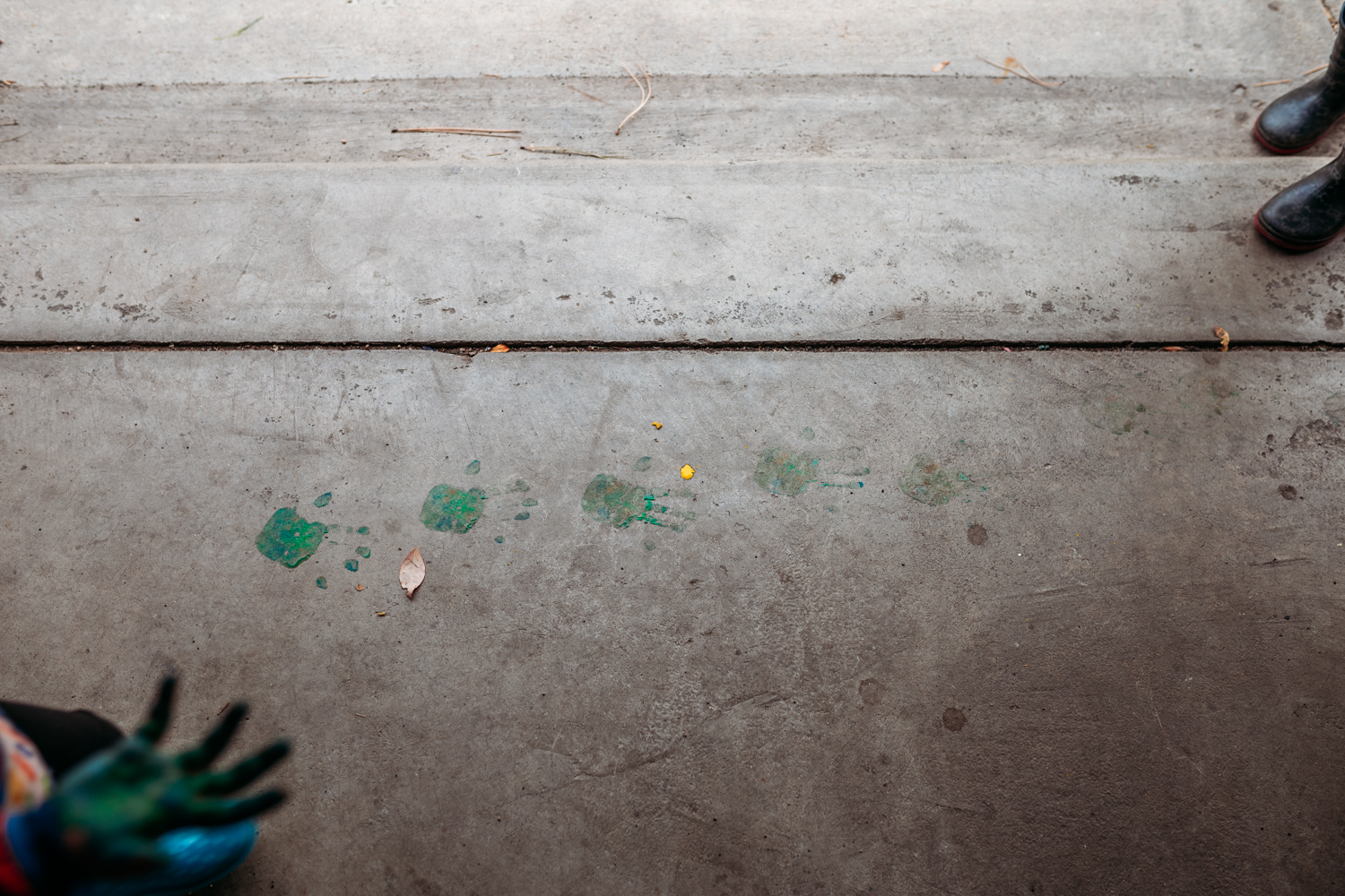 """Little girl's painted hands in bottom left hand corner of image, with painted handprints on concrete """"walking across"""" to top left corner with brother's boots."""