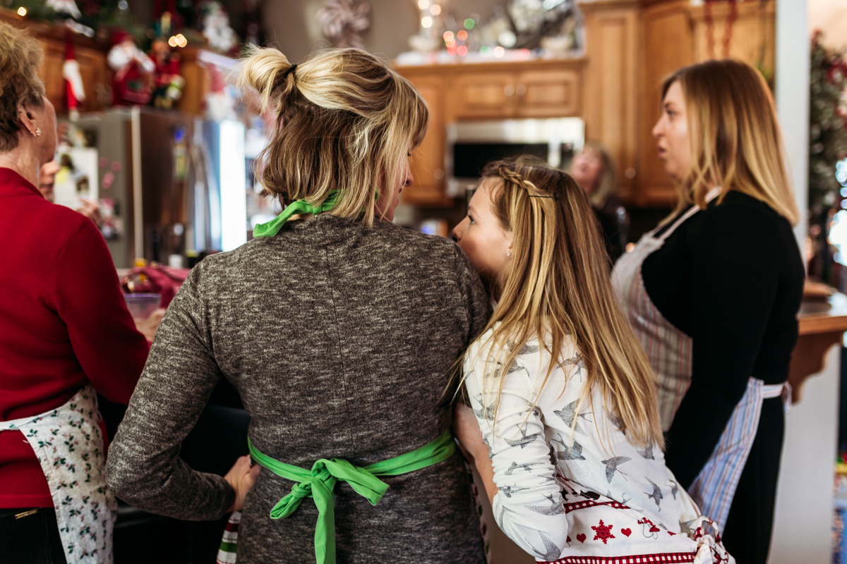 Girl looking up at her mother and hugging her wearing holiday aprons