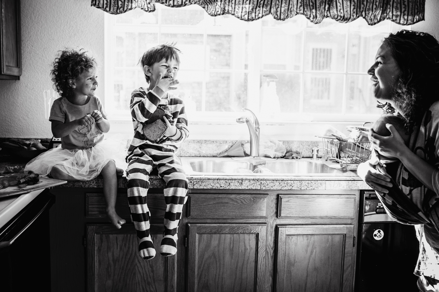 Mom wearing baby and smiling to her two children sitting on the counter