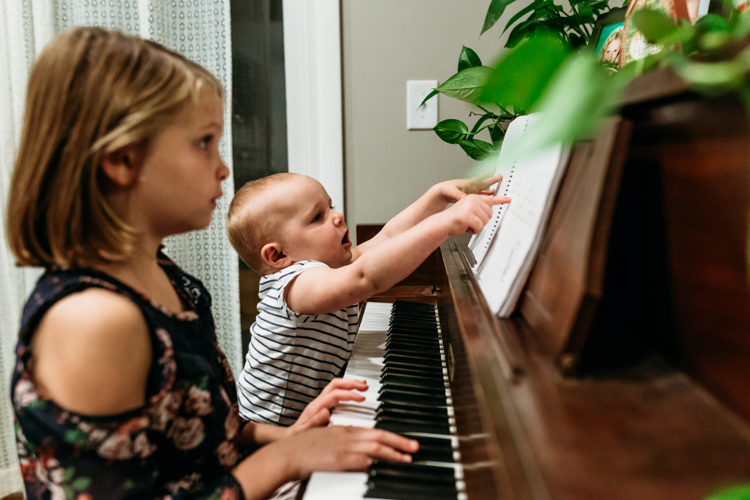 Side view of a girl with her baby sister sitting on the piano bench playing the piano