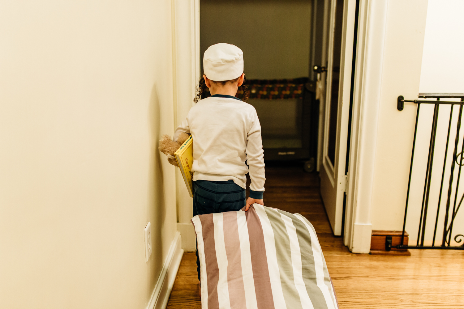 Little boy wearing pajamas walking in the hallway, pulling his pillow and holding a book and his teddybear