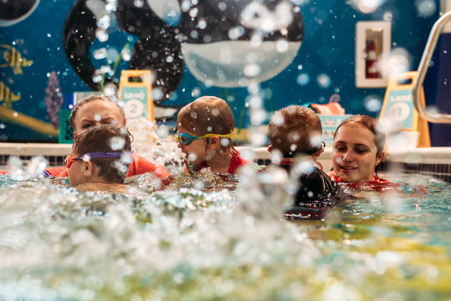 Childrens splashing in the water during swimming lessons at Goldfish Swim School in Brookfield, Wisconsin