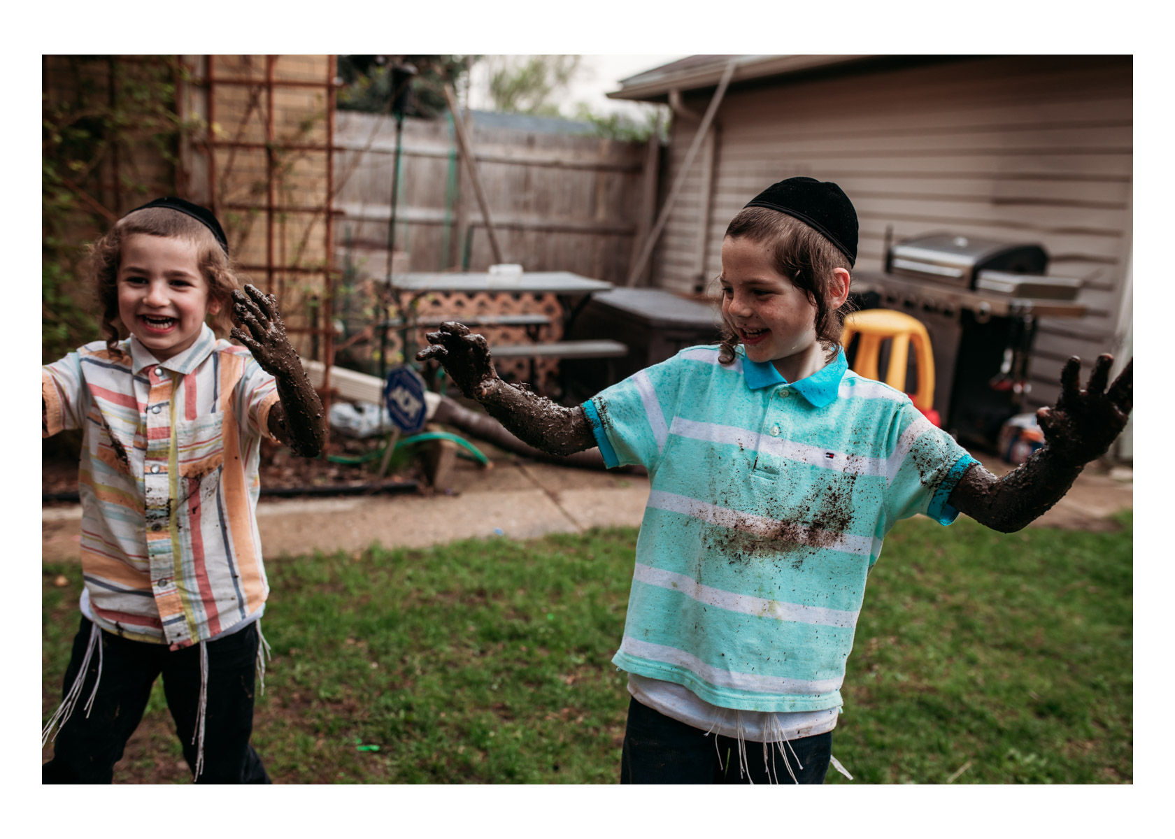 2 boys with wet mud all over their arms laughing in their backyard in Milwaukee