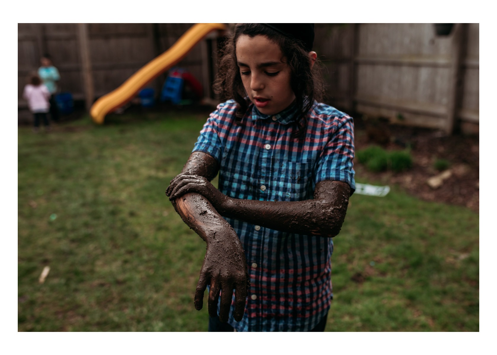 9 year old boy rubbing wet mud all over his arms in Milwaukee in May