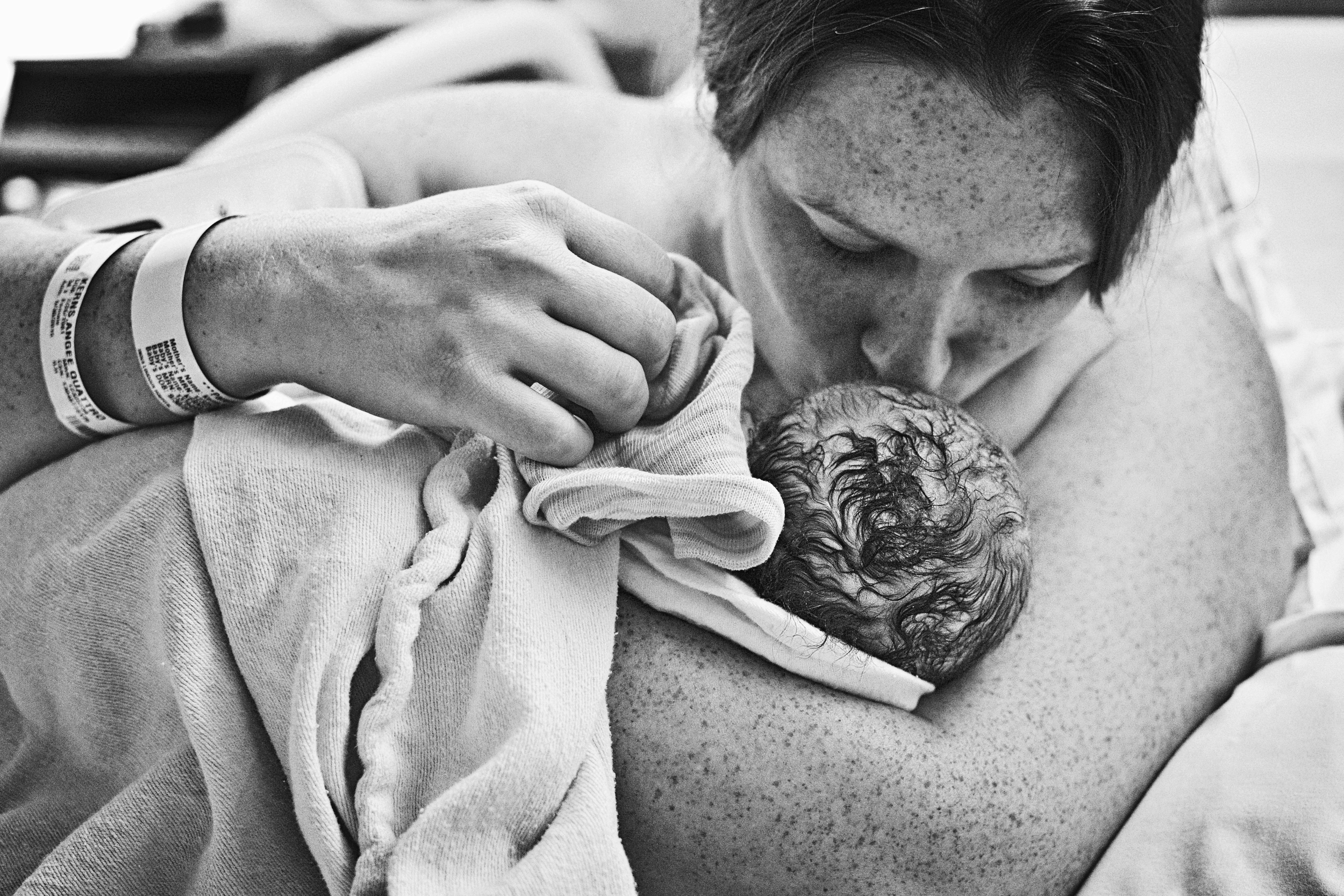 freckled mama kisses baby for the first time after labor