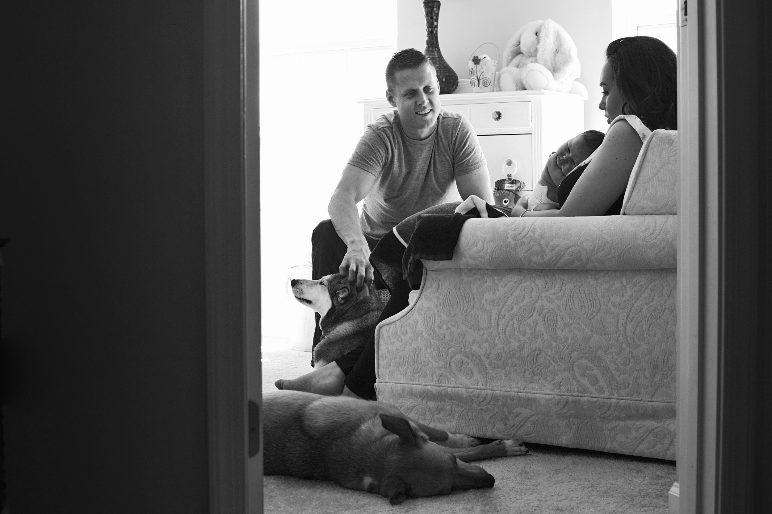 First time mom nurses her baby in the nursery with daddy and the dogs during their family session in Mechanicsville.