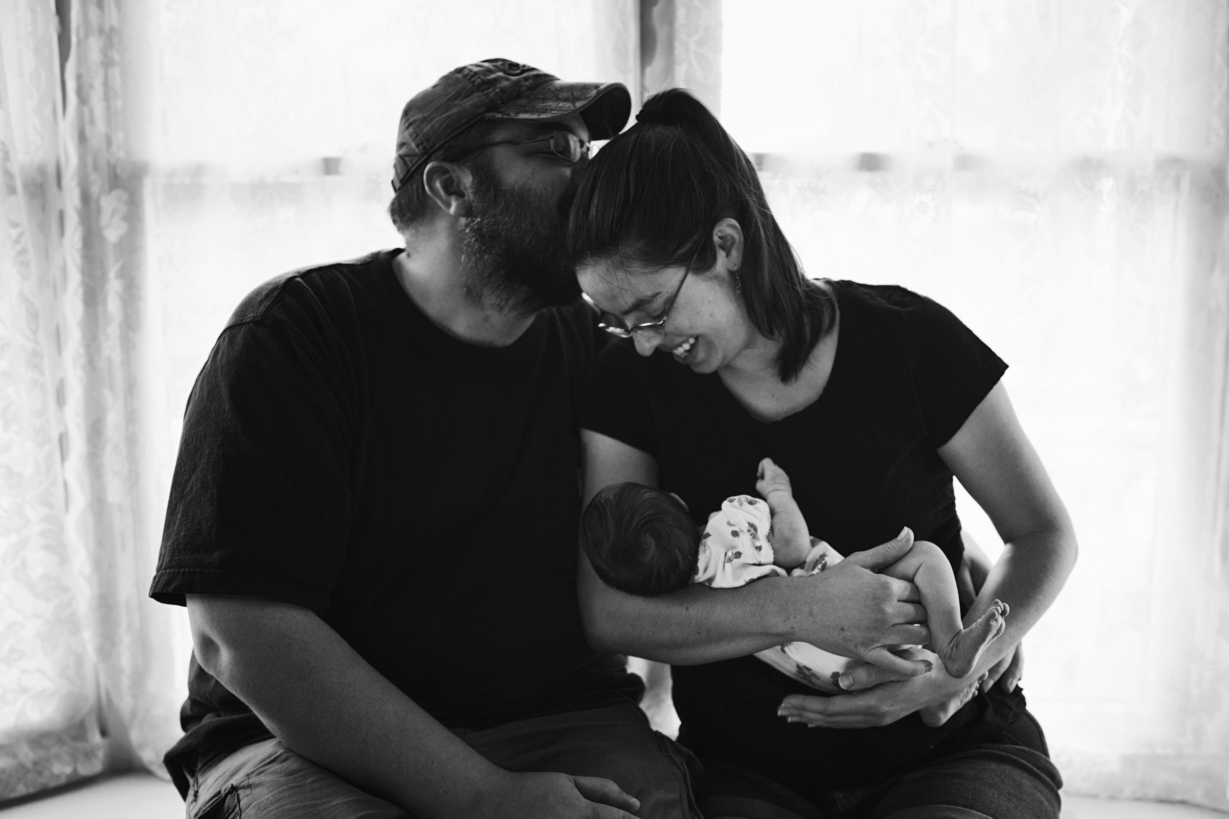 Short Pump mom and dad cuddle with their newborn at home after a brief stay in the NICU during their lifestyle newborn session.