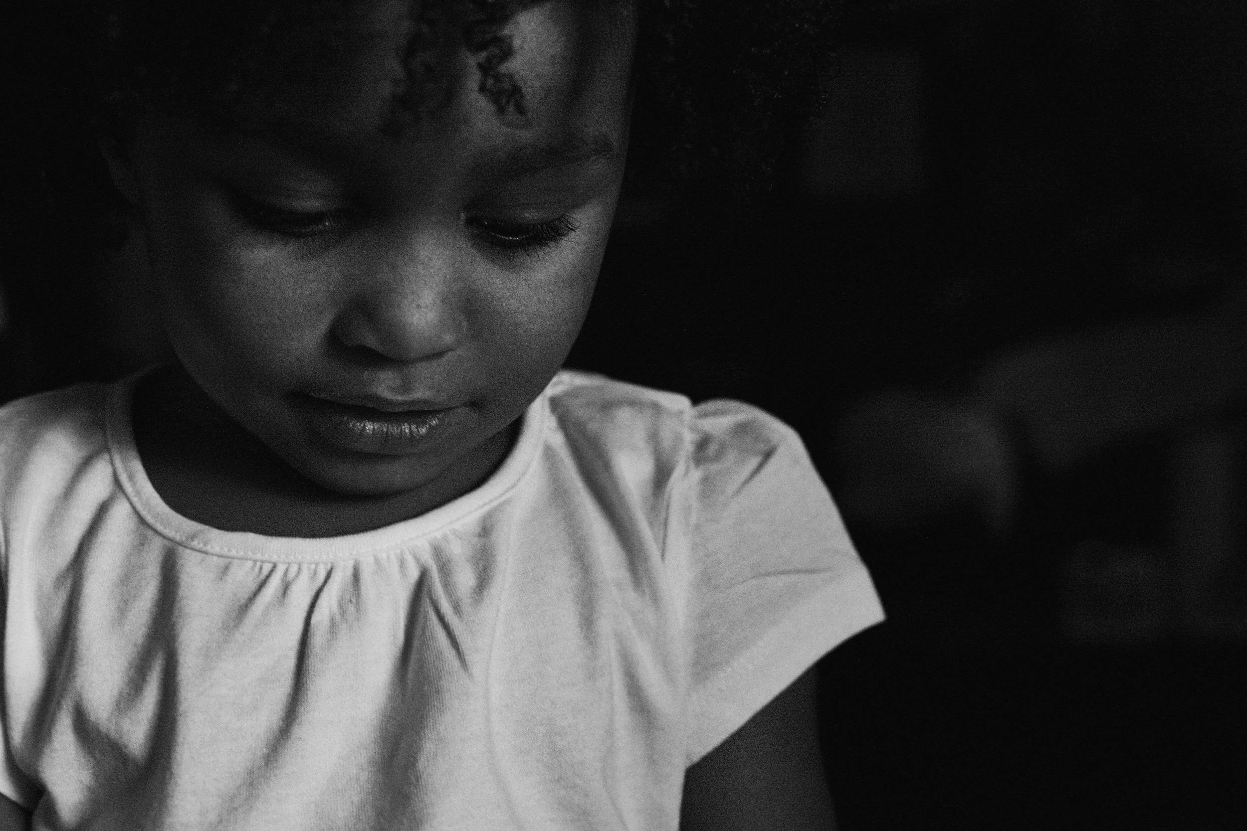 Sweet black girl look down as she focuses on her toes during a portrait session with her mom and sister.