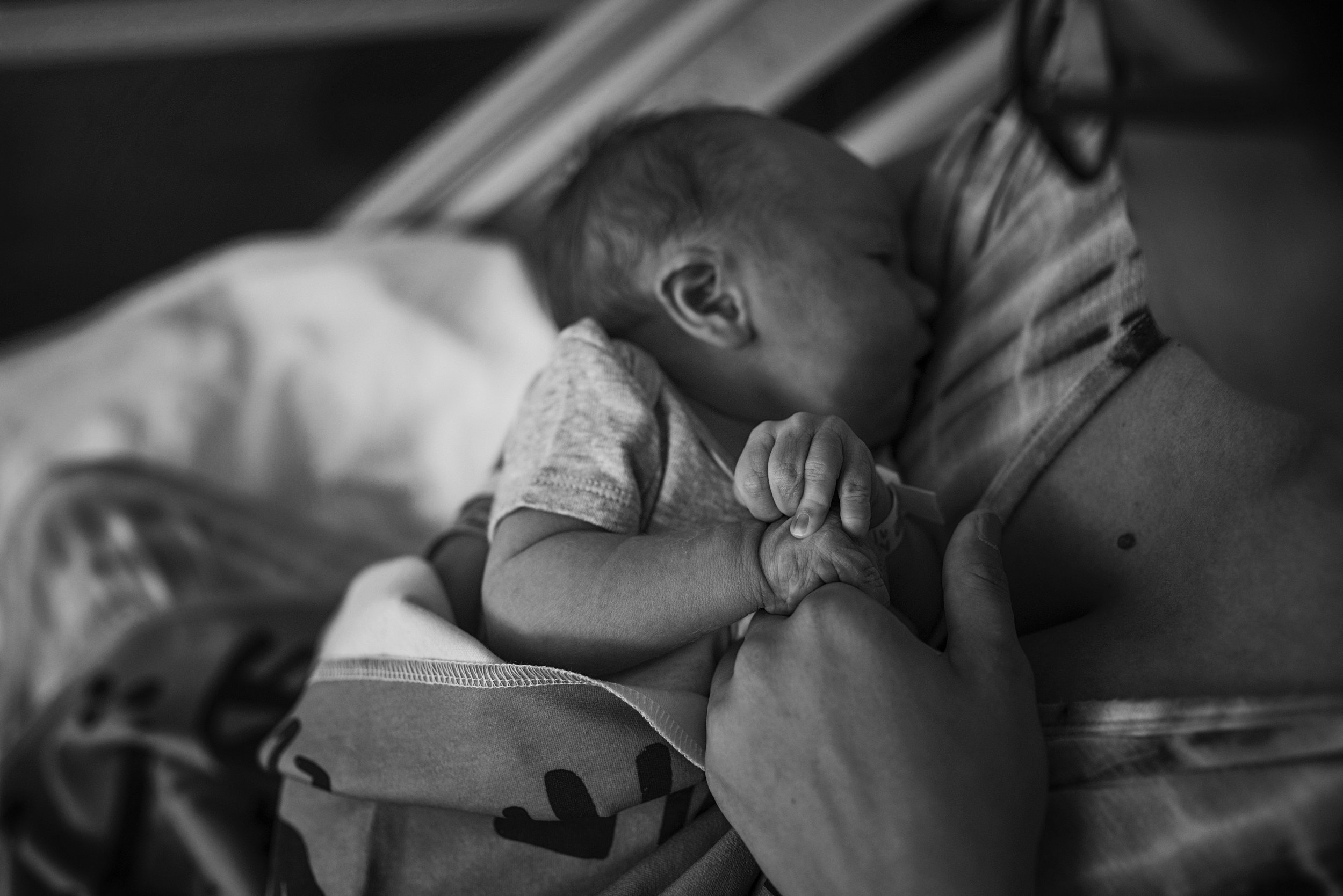 Baby boy grasps mom's hand after breastfeeding during their Richmond Fresh 48 photography session.