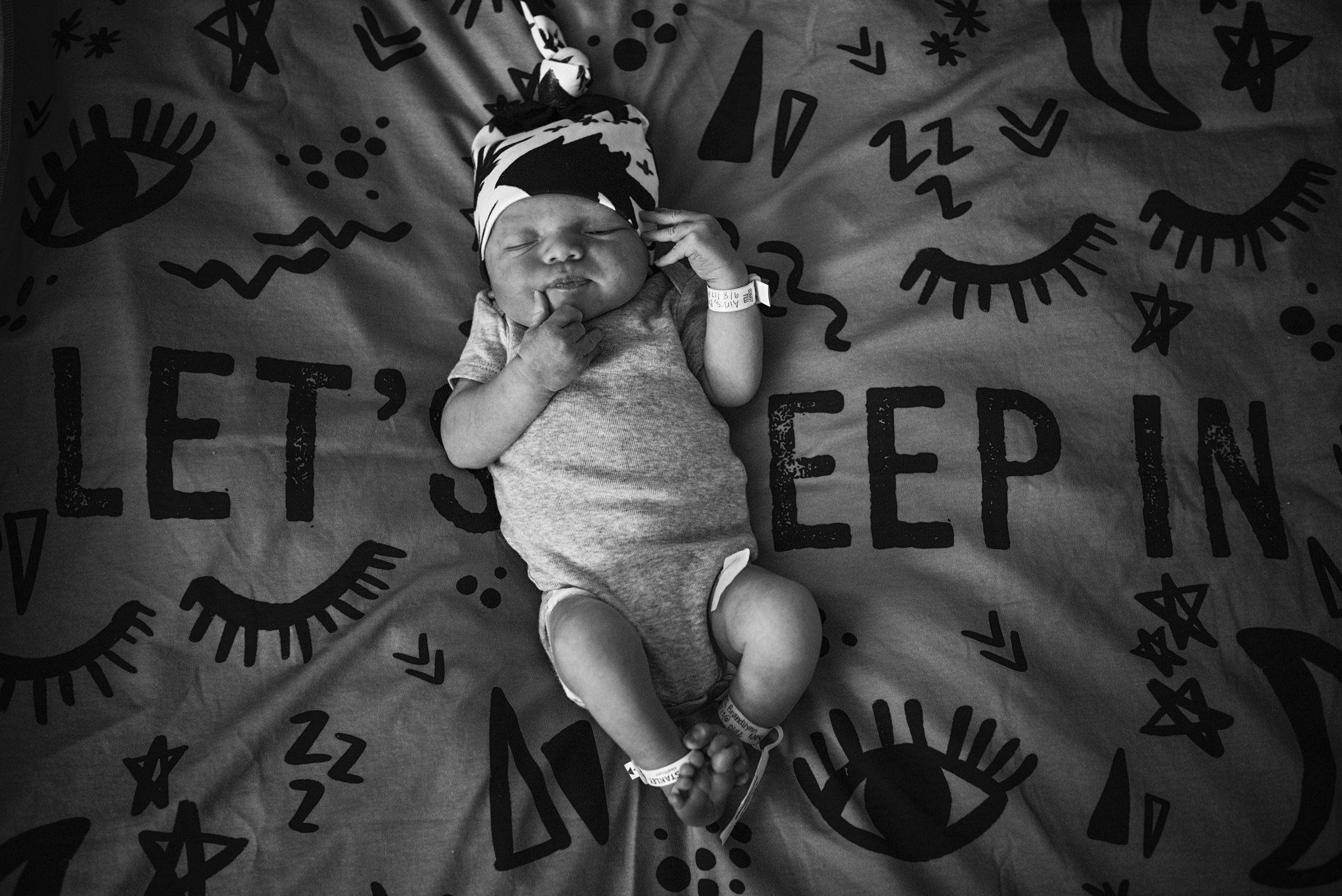 Sleepy newborn baby boy on his blanket during a Fresh 48 session by family photographer, Nicoleinbold.