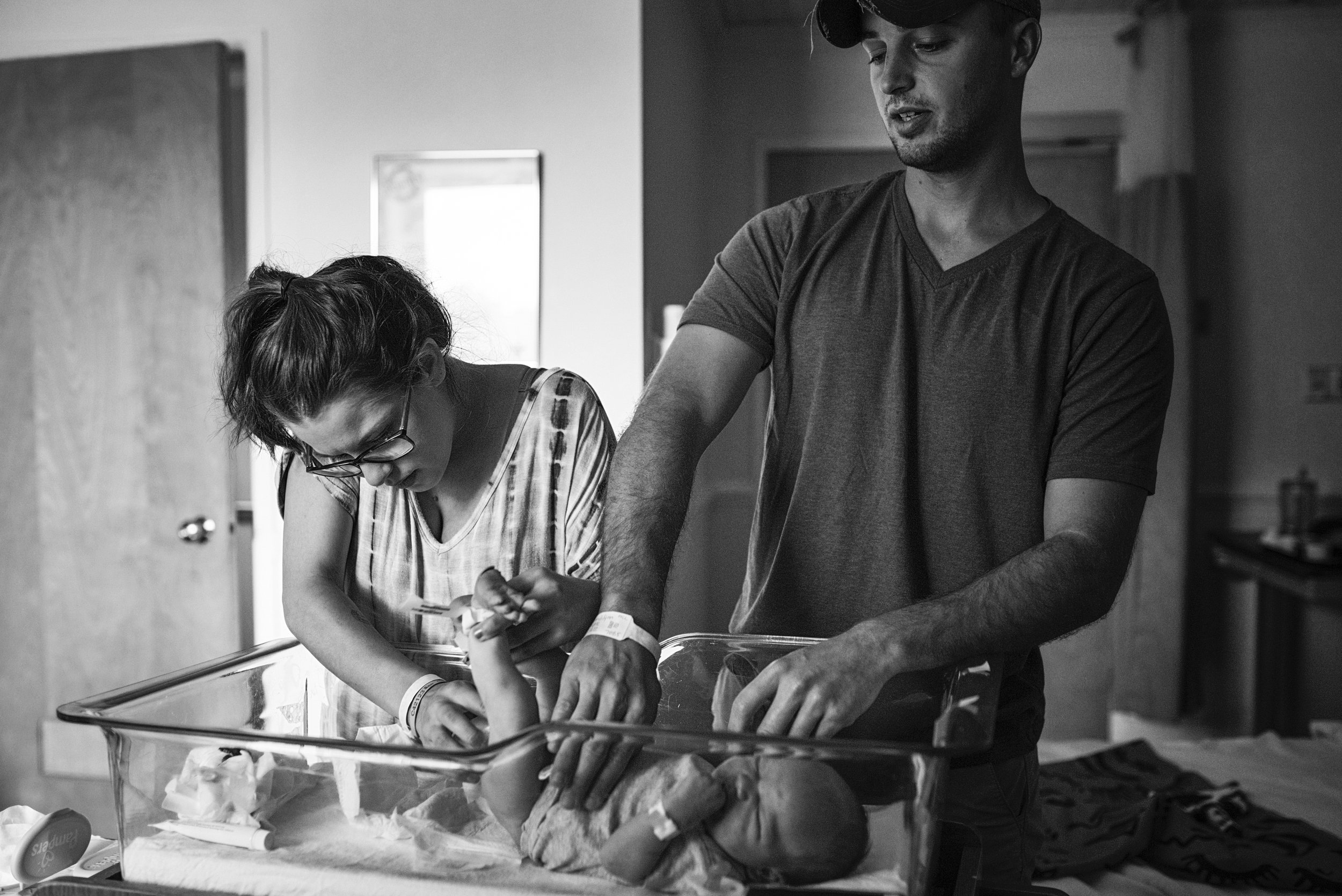 Documentary family photographer takes picture of mom and dad changing their first diaper together in a Richmond area hospital.