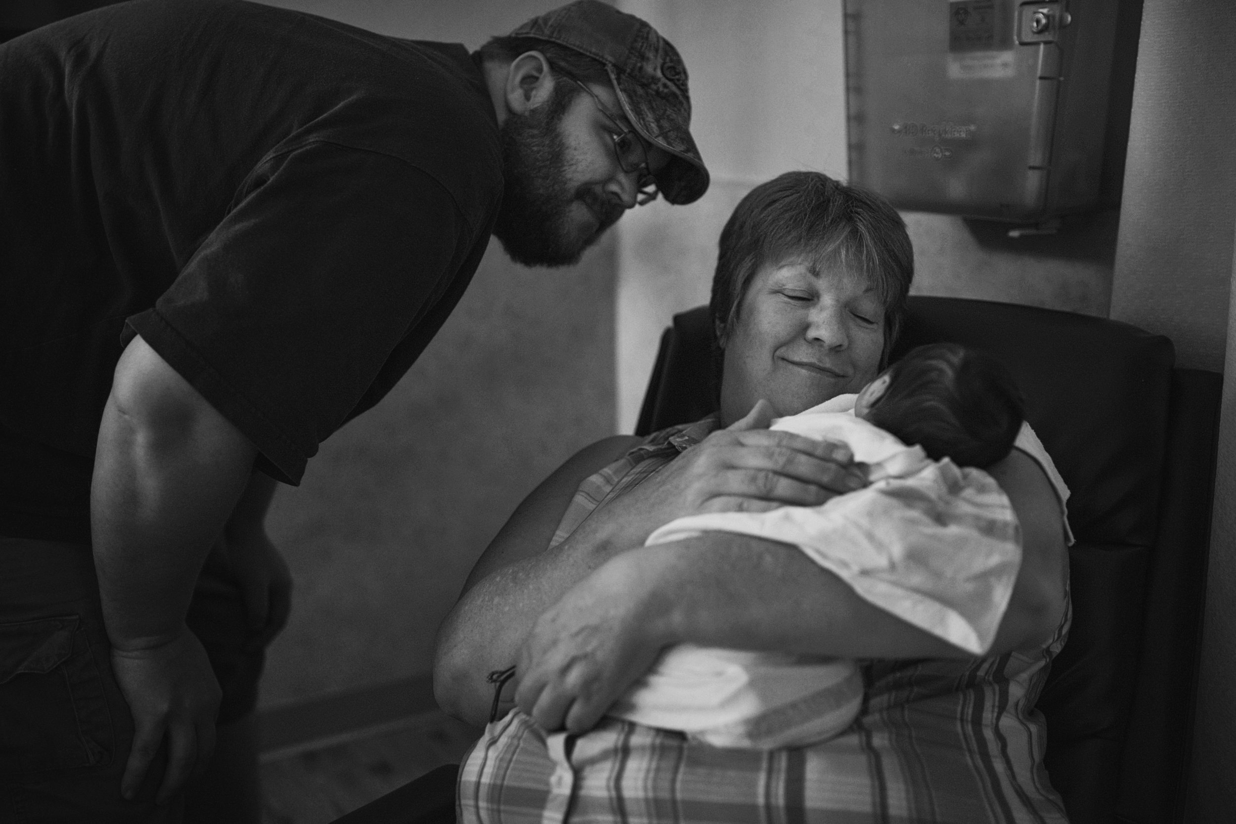 Best Richmond family photographer takes images of dad showing off his newborn baby daughter to his own mother.