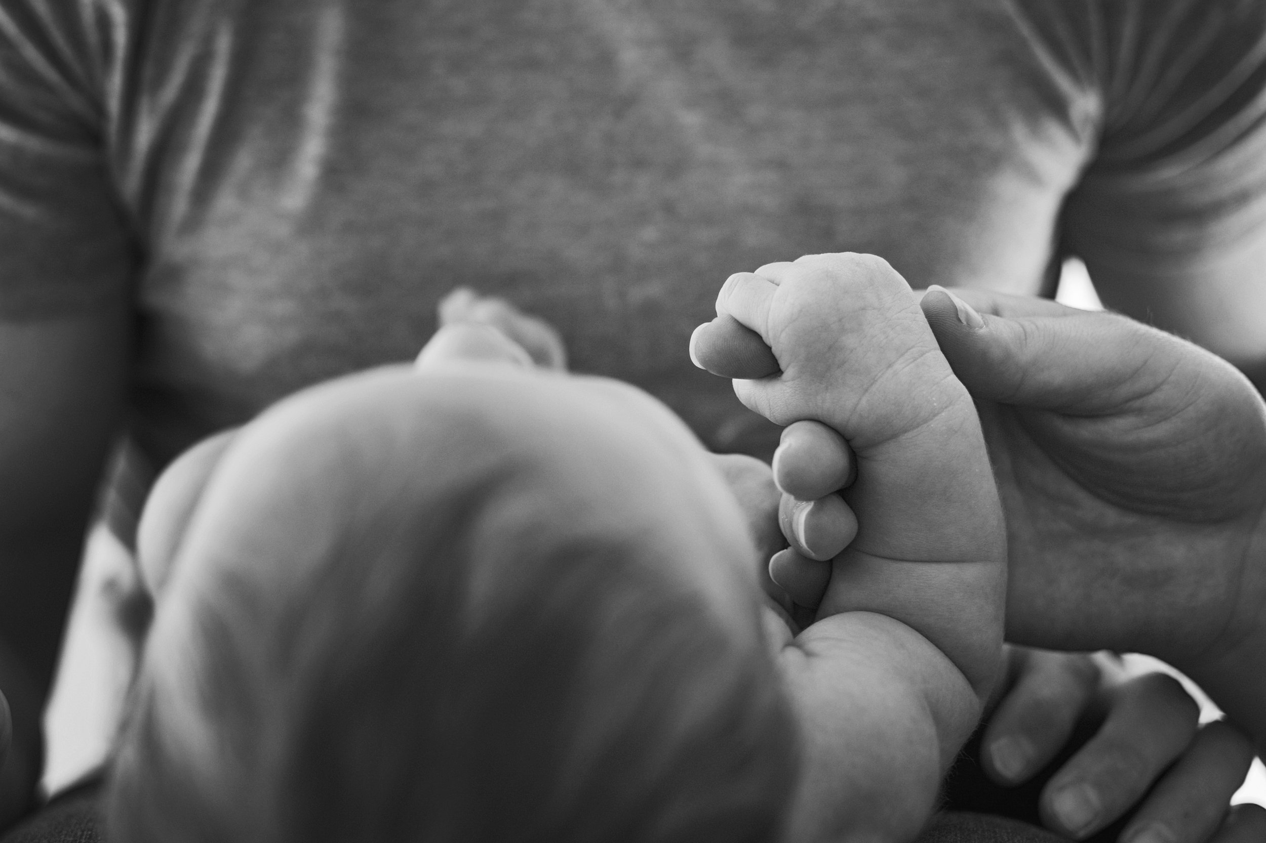 Central Virginia's best family photographer documents a baby grasping his mom's finger while laying on dad's lap.
