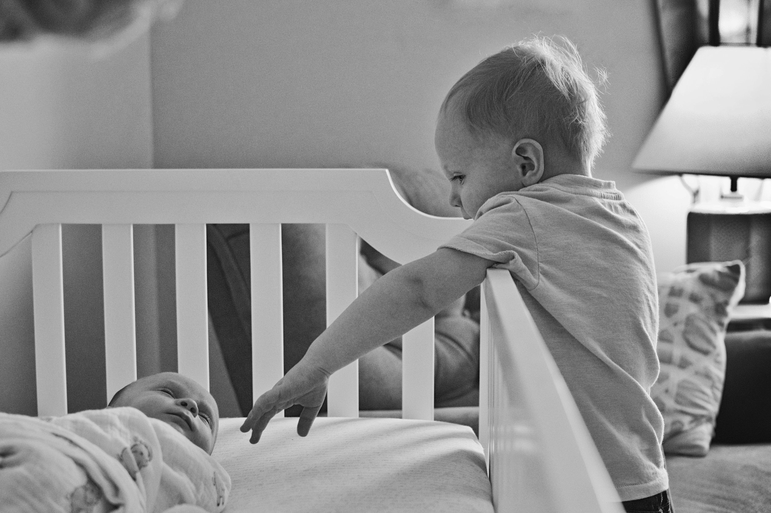 At a Glenn Allen home, a big brother reaches into his baby sister's crib to say hello during an in home lifestyle new life session.