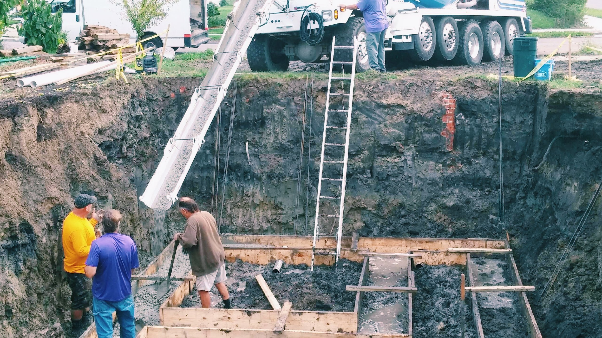 """Here we are having a delivery of cement to make the footings. The hole was 40' long, 20' wide and 9' deep. You can not see it here, but we have a 10"""" deep 10' x 4' cavity in the floor that holds pea gravel and water. This inner reservoir of water is what creates the high 80-90 percent humility we need to over winter dahlia and gladiola tubers. The root cellarBeing embedded this deep in the ground ensures that the inner temperature of the root cellar will not exceed 50 degrees, perfect for dahlias."""