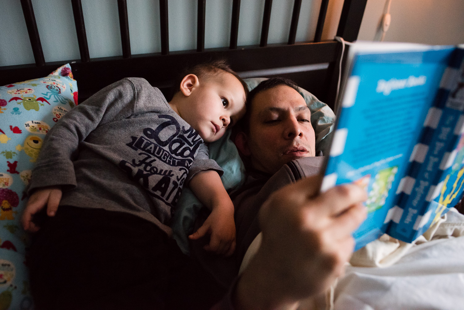 Alexandria Virginia family lifestyle and documentary photography, father and son snuggle while reading in bed