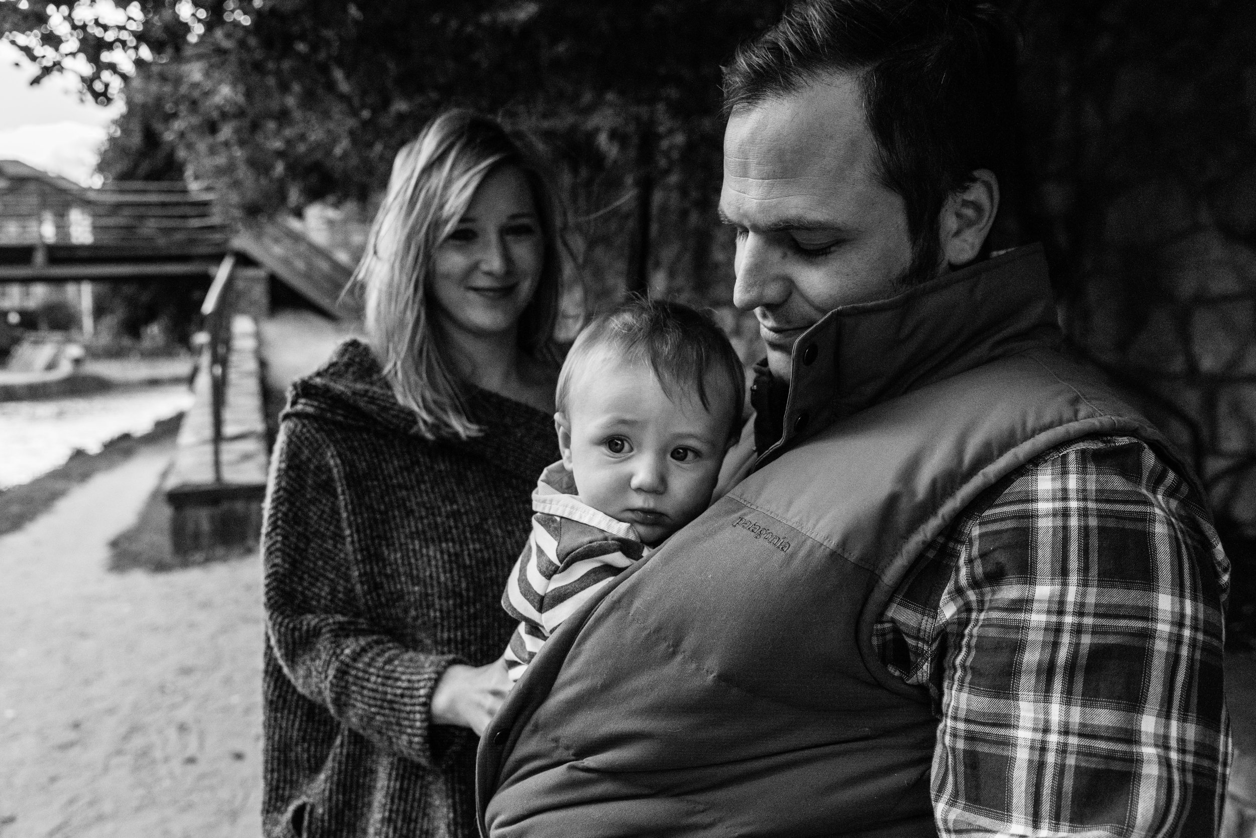 Mom snuggling baby with Dad watching | Nicole Sanchez Family Documentary Photographer