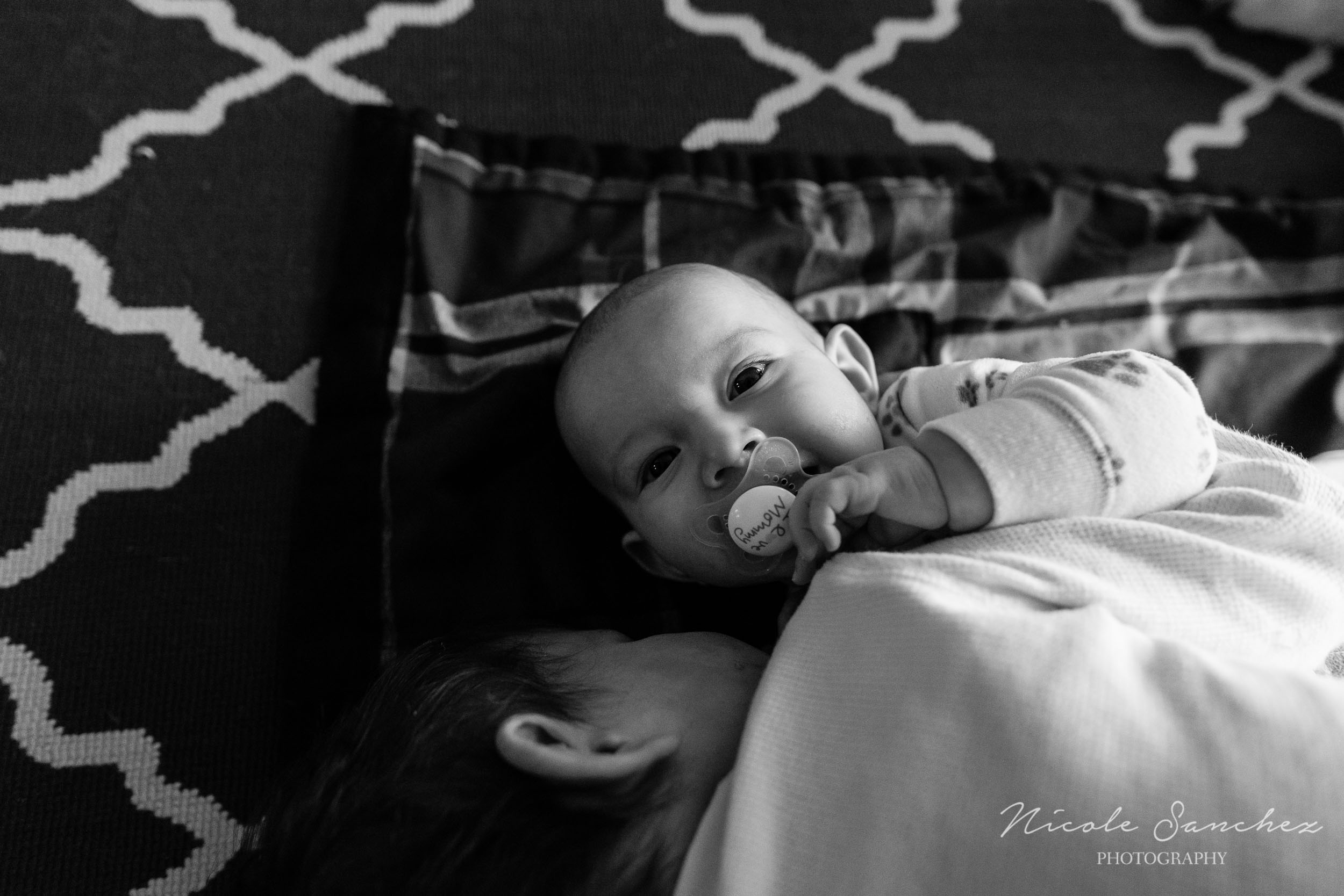 Baby boy smiling with pacifier in mouth by Northern Virginia Lifestyle Photographer Nicole Sanchez
