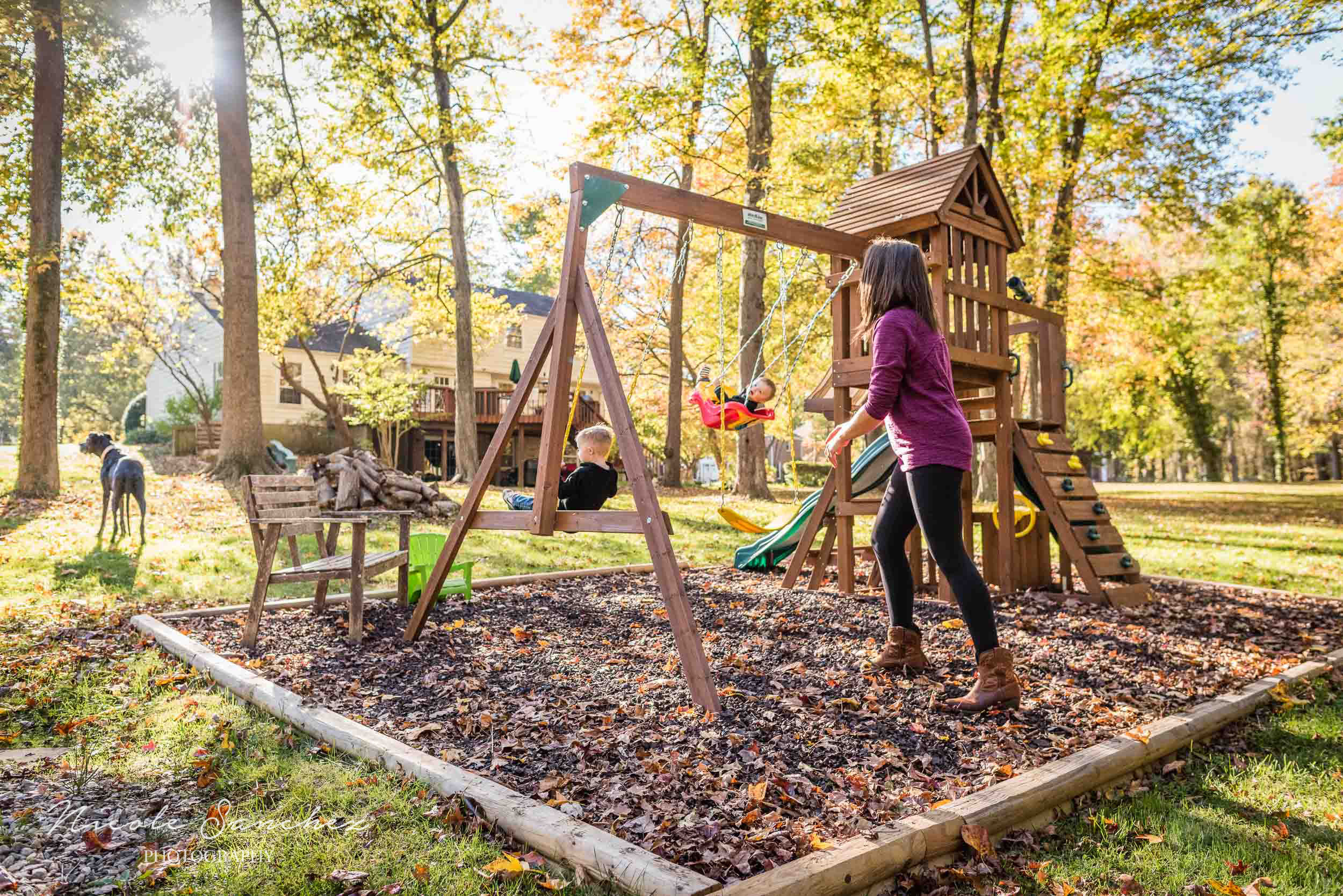 Mom pushing two sons in swings in backyard playground in Northern Virginia by Family Photographer Nicole Sanchez