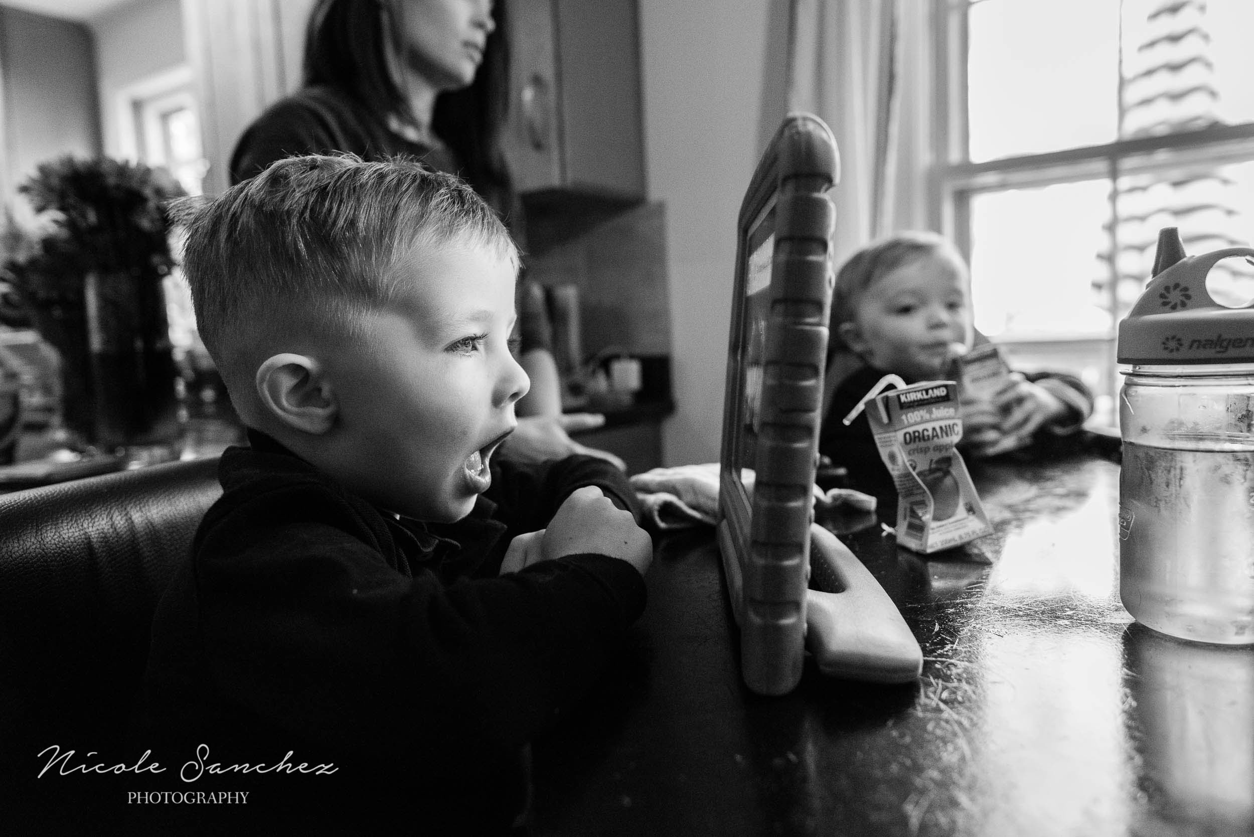 Young boy playing on tablet in kitchen during in-home family photography session by Nicole Sanchez