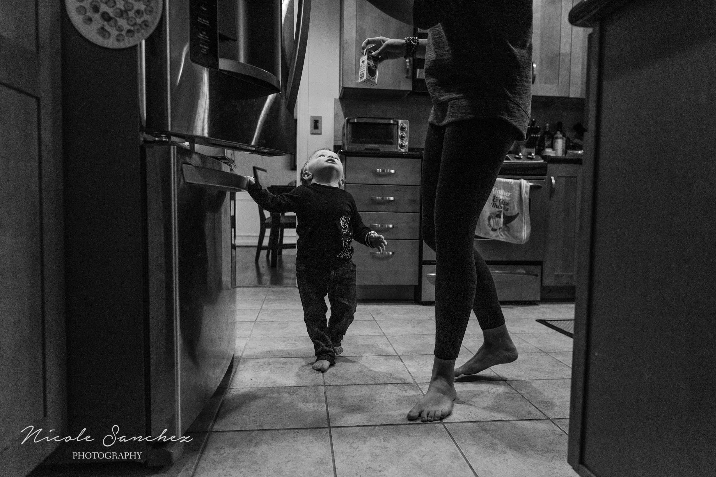 Toddler waiting for mom to give him juice in kitchen at in-home photography session by Documentary Family Photographer Nicole Sanchez
