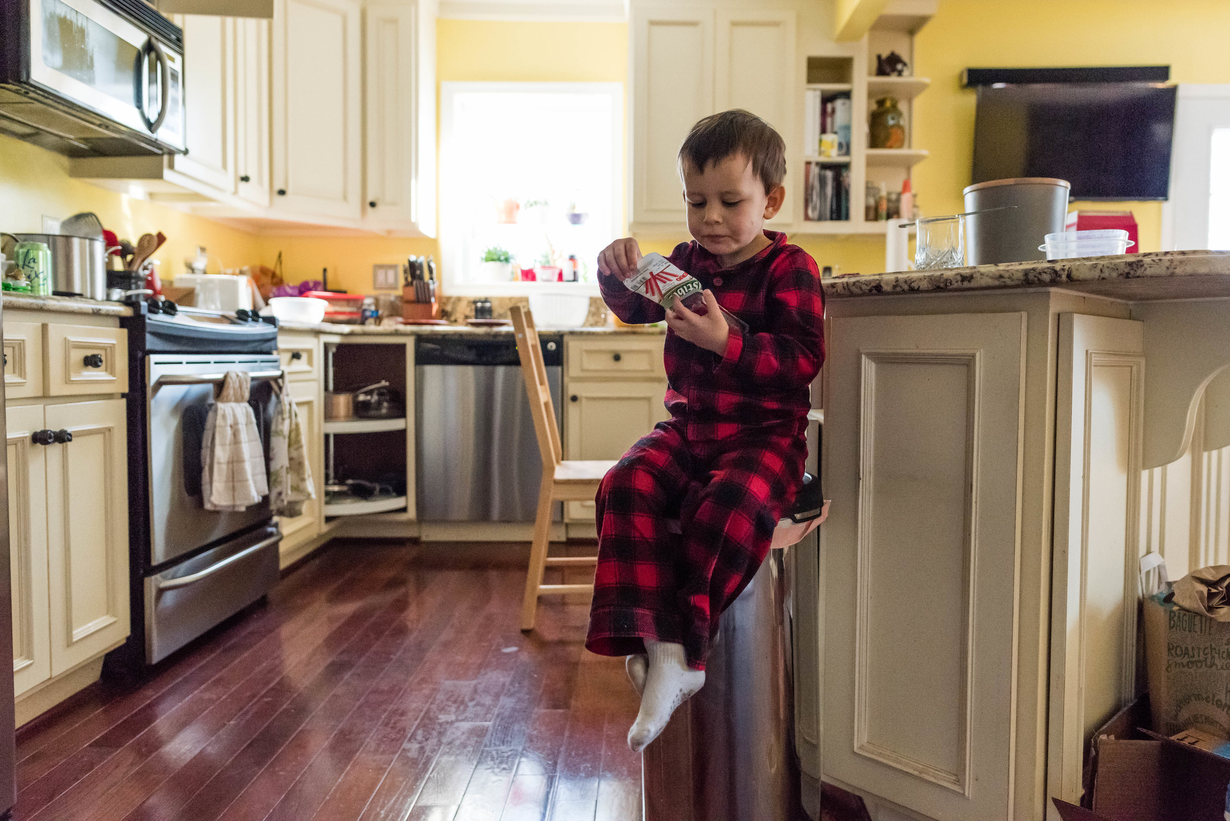 Boy eating yogurt on kitchen trash can in Northern Virginia by Nicole Sanchez Photographer