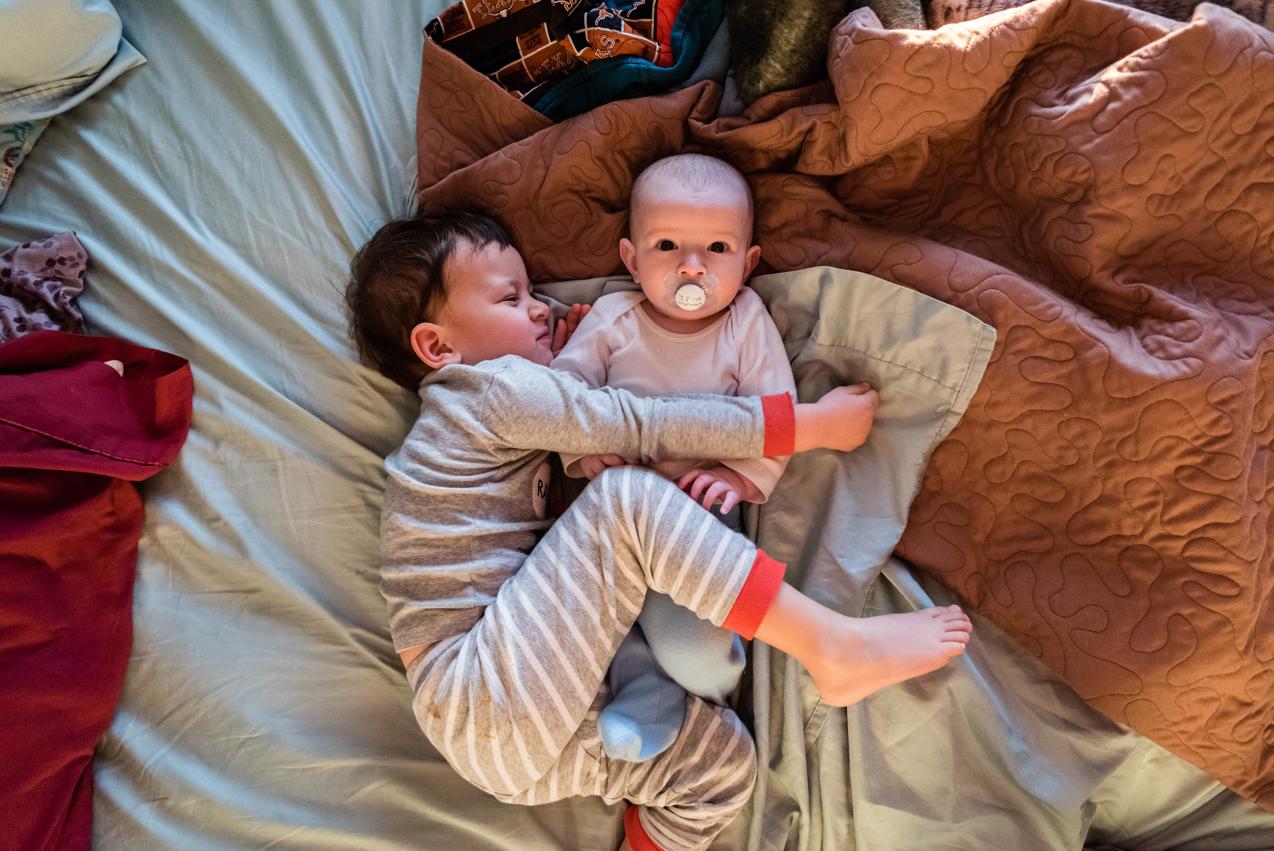 Brothers cuddling on bed in Alexandria, VA by Family Photographer Nicole Sanchez