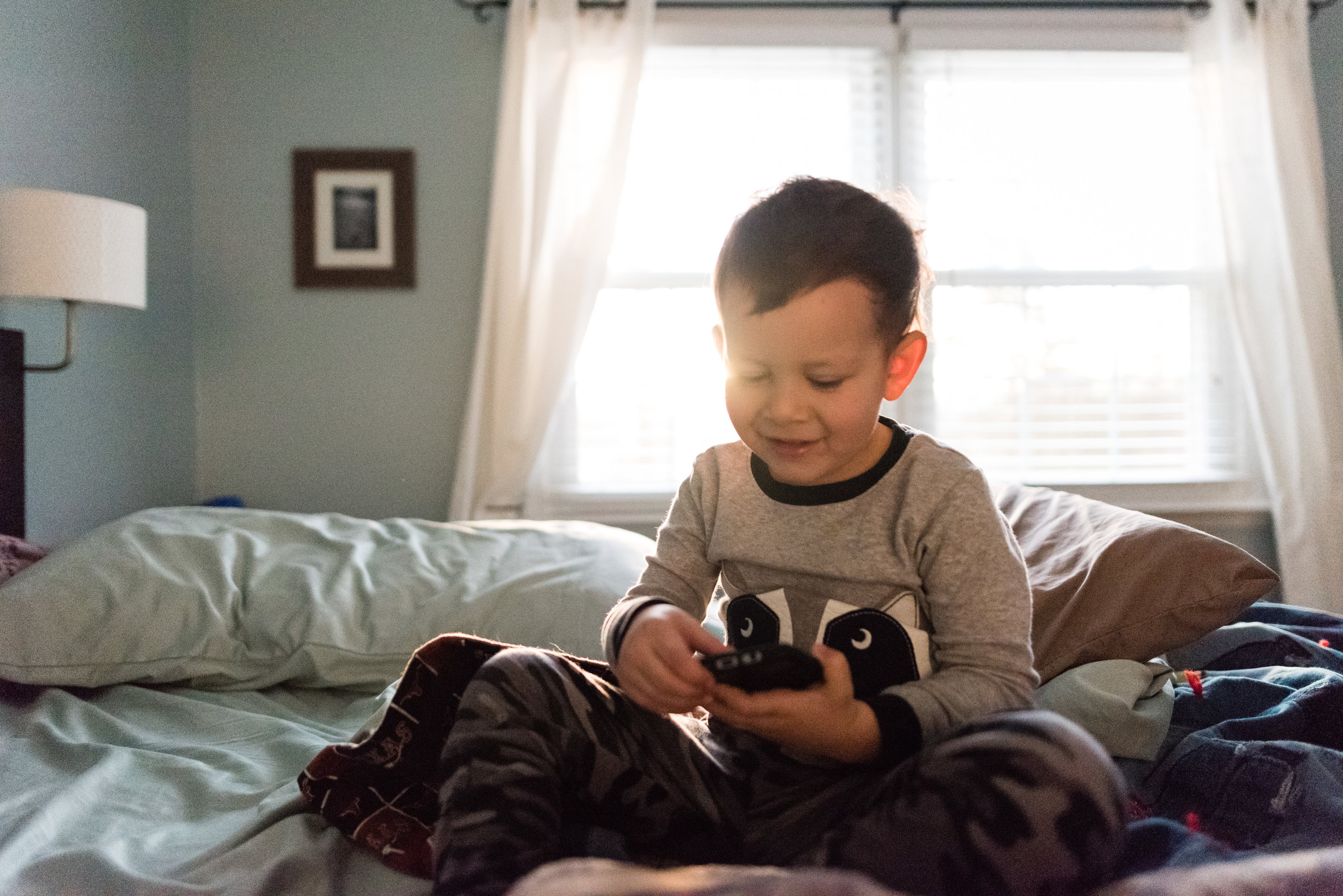 Boy texting on bed by Alexandria, VA Family Photographer Nicole Sanchez