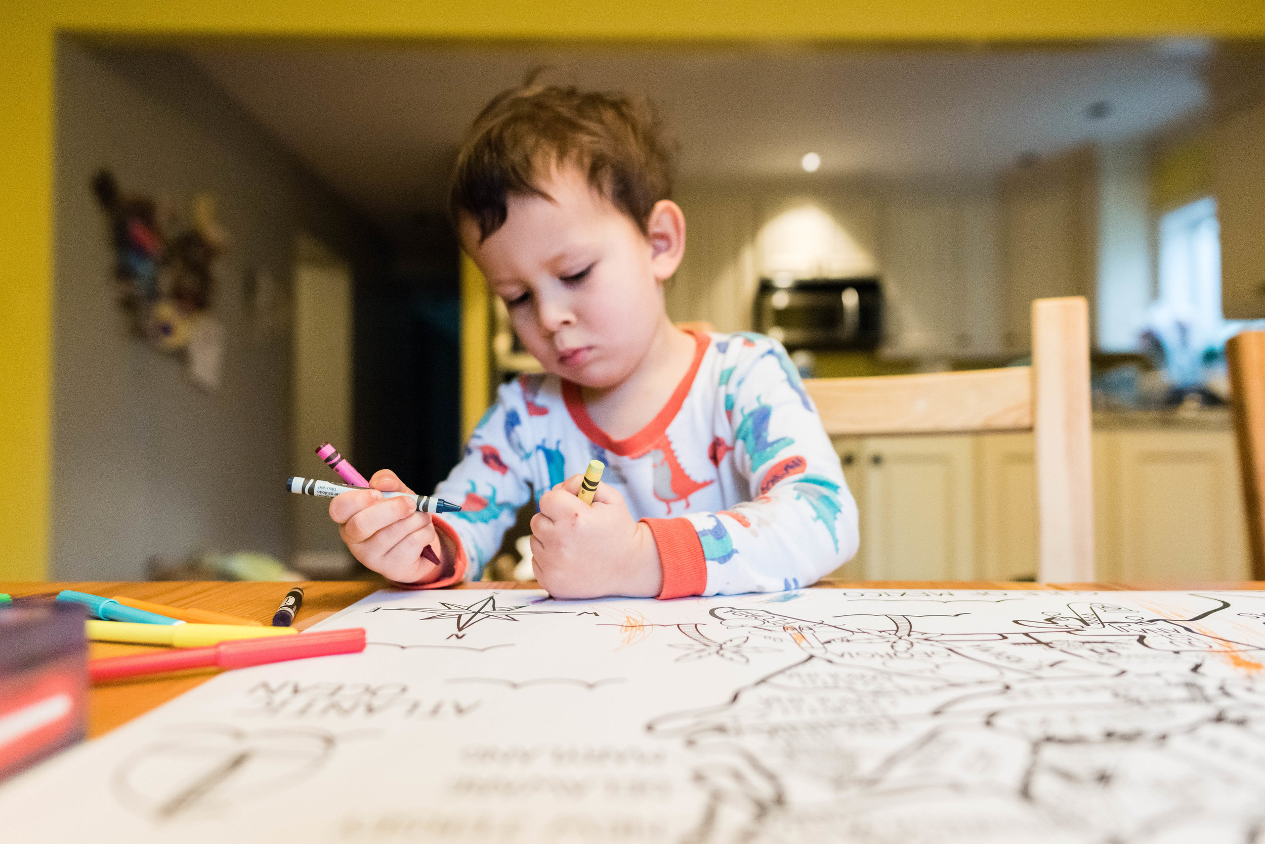 Boy coloring at kitchen table in pajamas by Nicole Sanchez Family Photographer