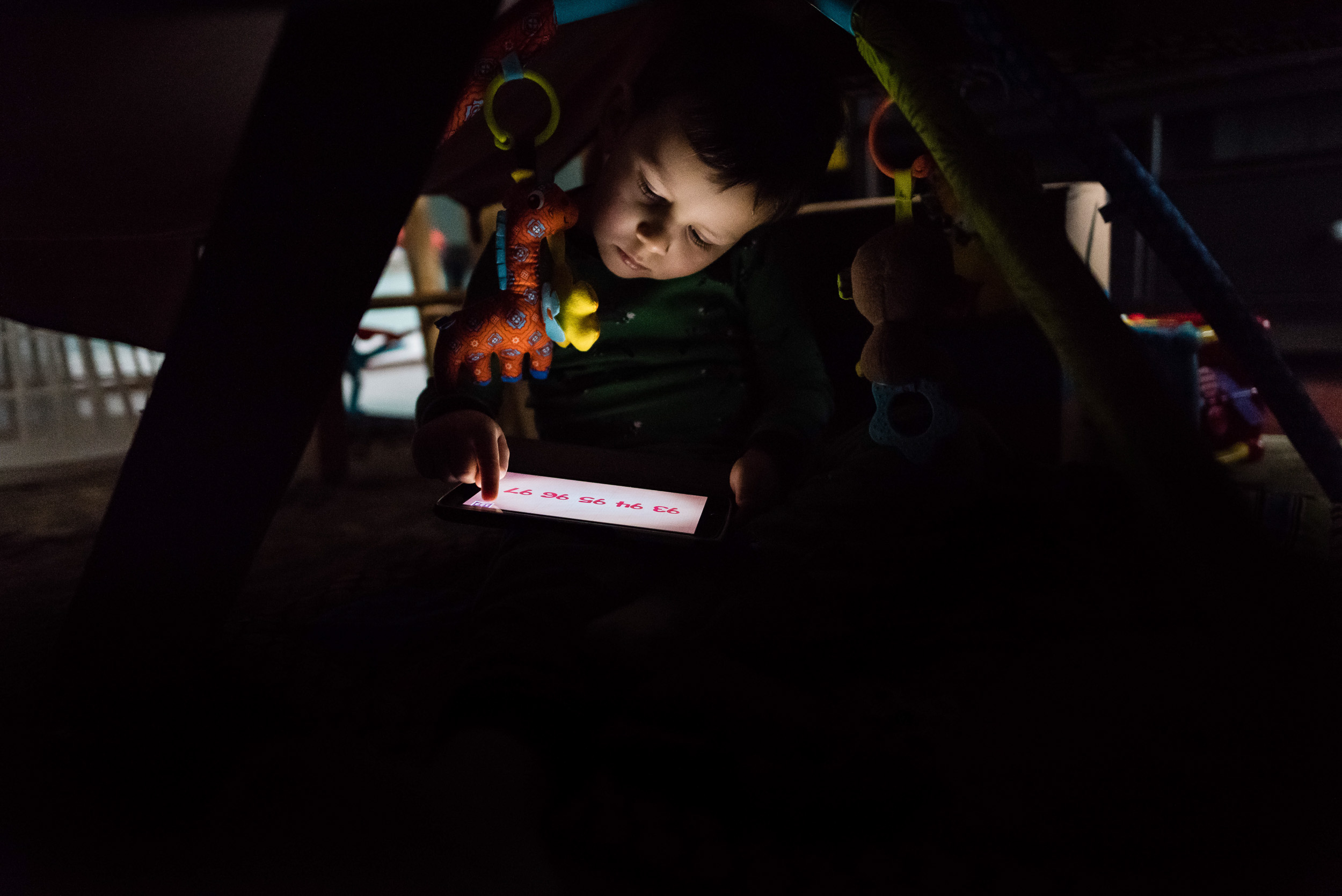 Boy playing with tablet under blanket fort by Northern Virginia Family Photographer Nicole Sanchez
