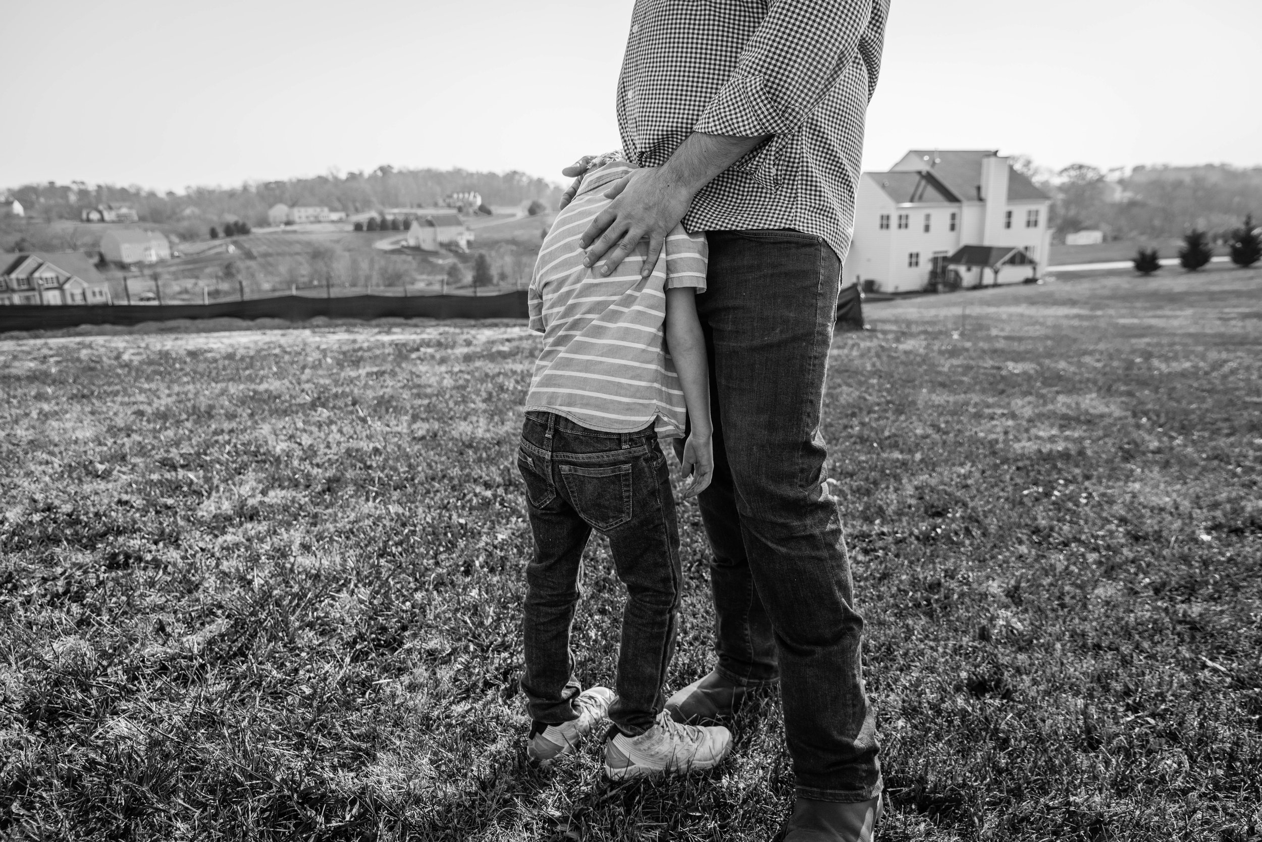 Candid moment of Dad comforting son by Northern Virginia Family Photographer Nicole Sanchez