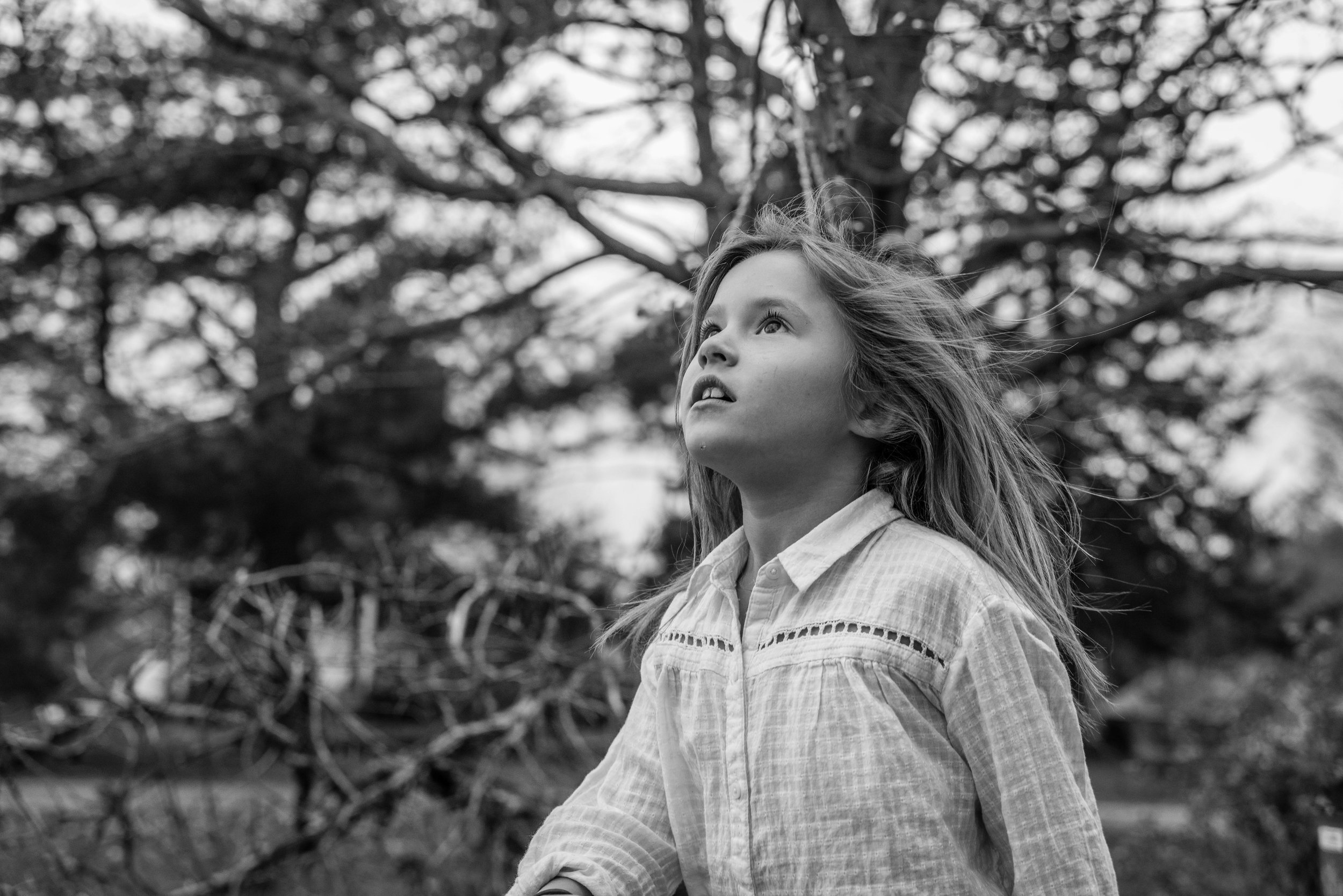 Girl chasing leaves with wind in her hair by Alexandria, VA Lifestyle Photographer
