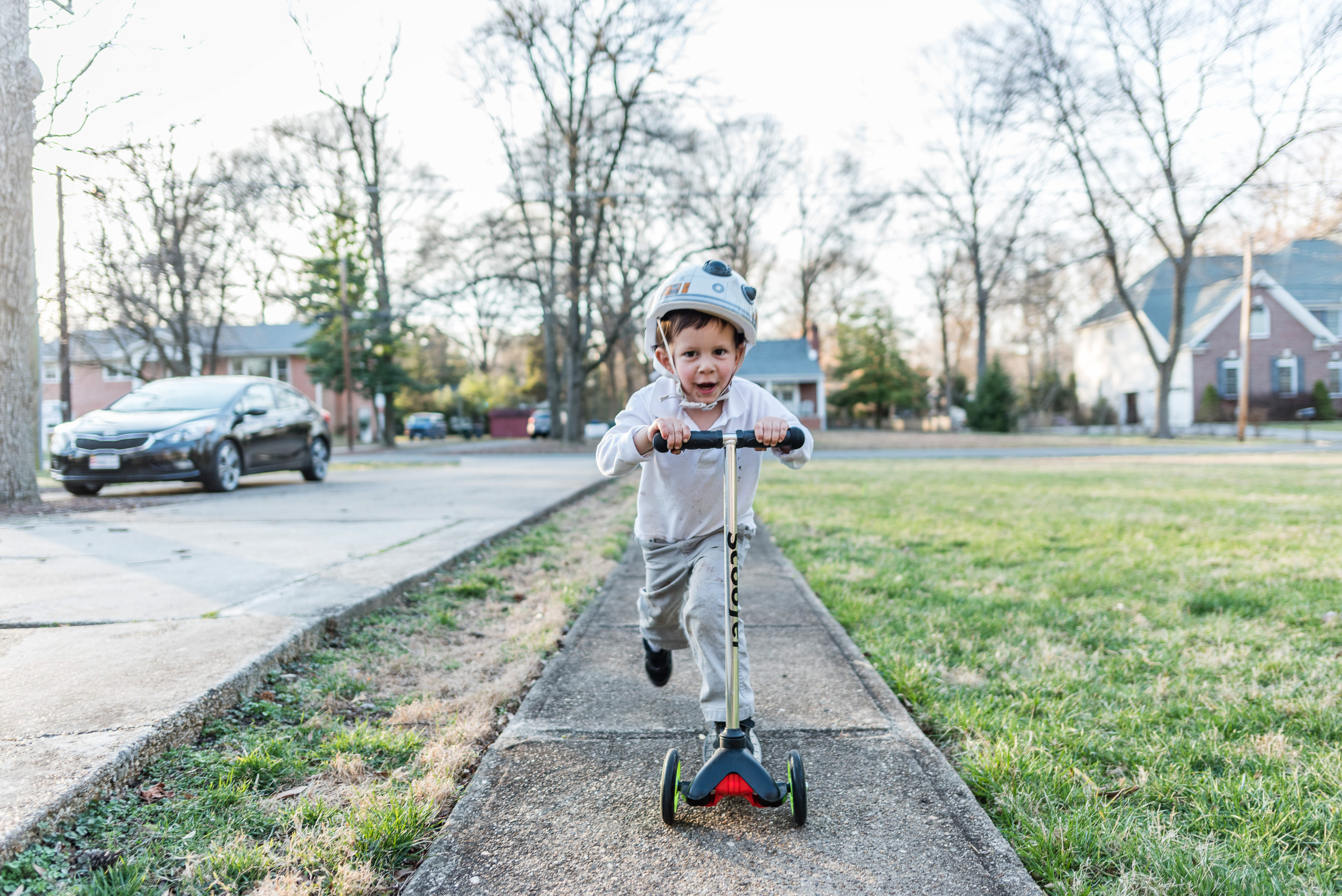 Boy riding scooter on sidewalk in Alexandria, Virginia by family photographer Nicole Sanchez