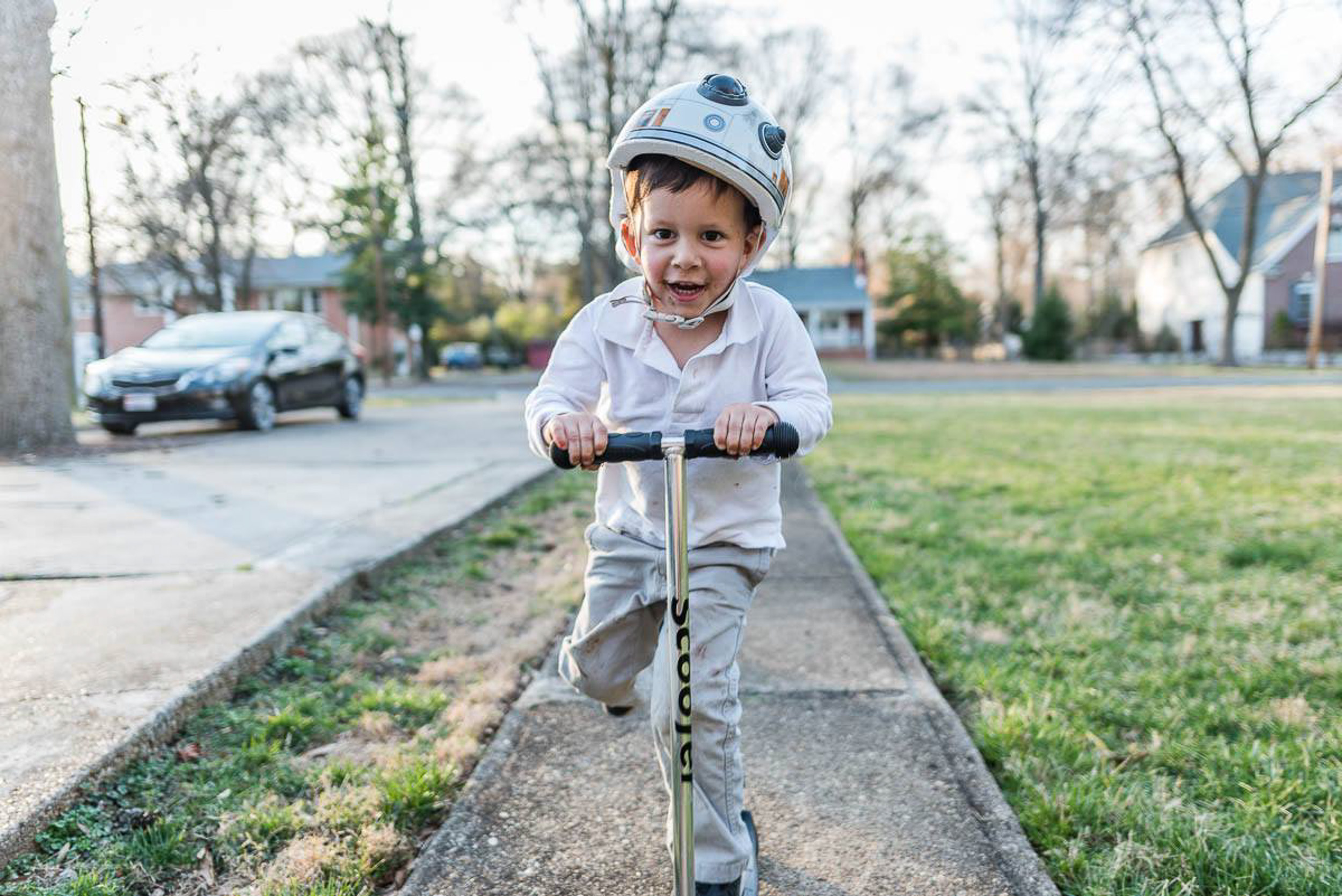 Boy riding scooter on sidewalk in Northern Virginia by family photographer Nicole Sanchez