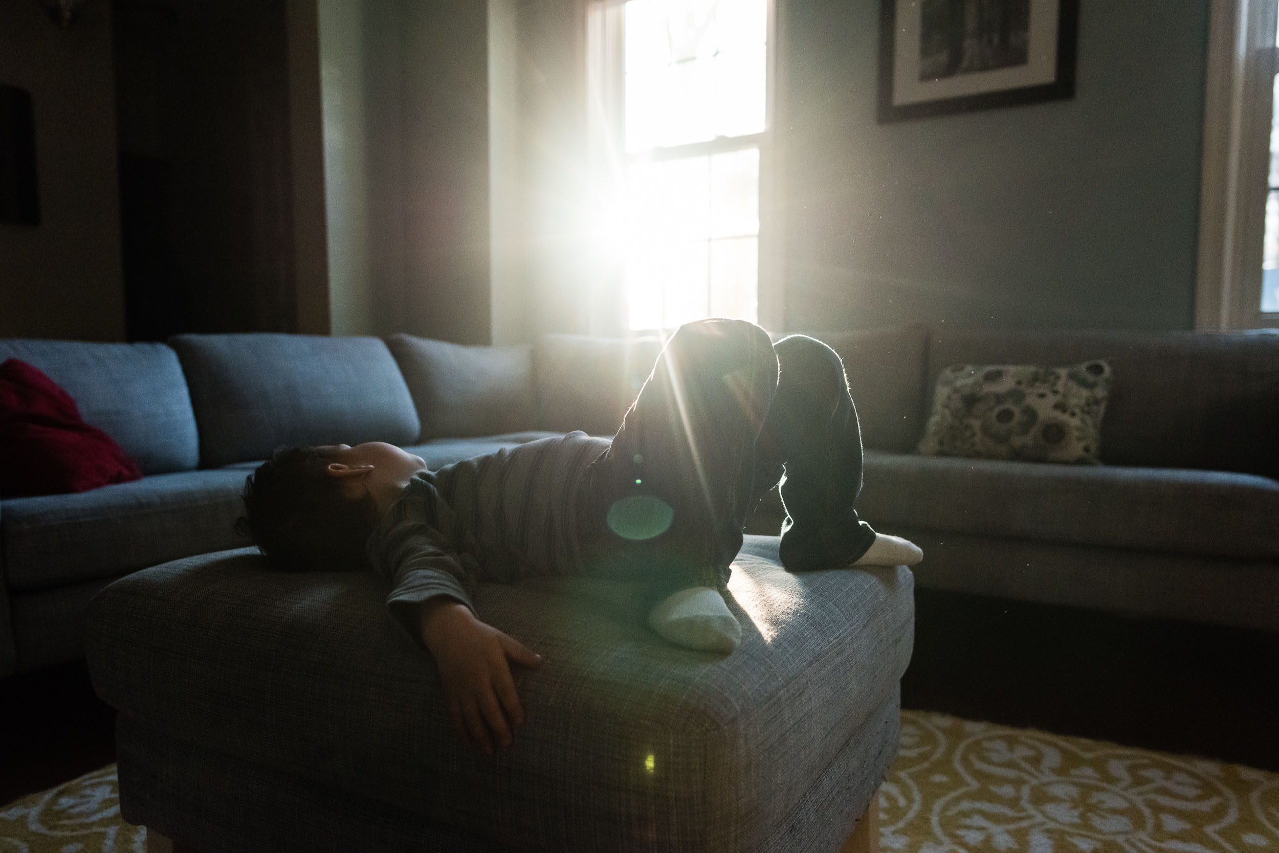 Boy resting on ottoman with sun flare by Northern Virginia Family Photographer Nicole Sanchez