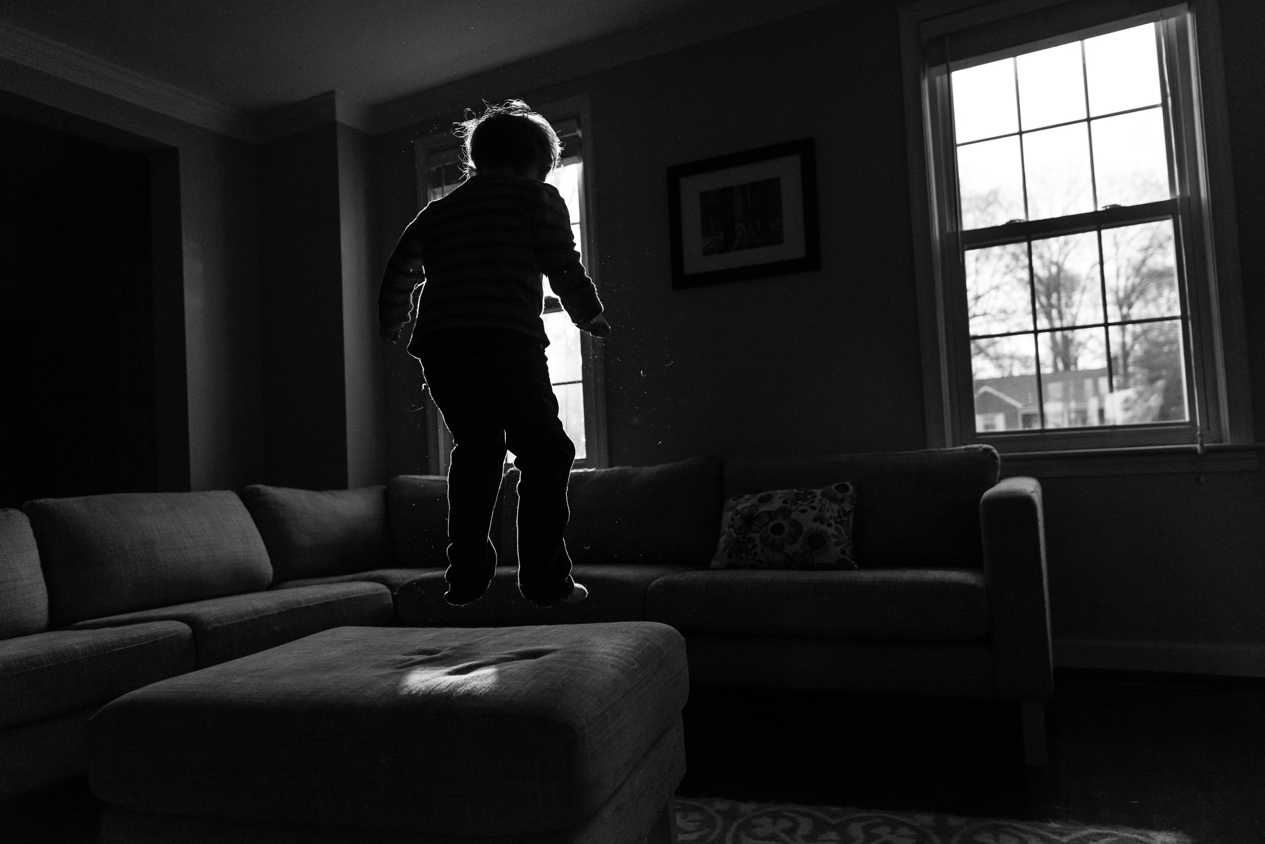 Boy jumping on couch with rim light by Northern Virginia Family Photographer Nicole Sanchez