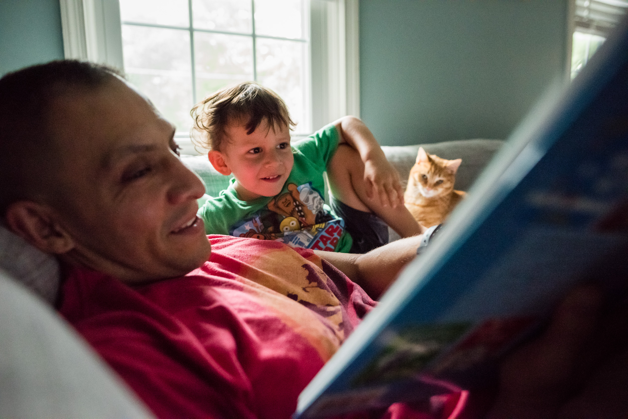 Boy and father reading with cat in Northern Virginia by family photographer Nicole Sanchez