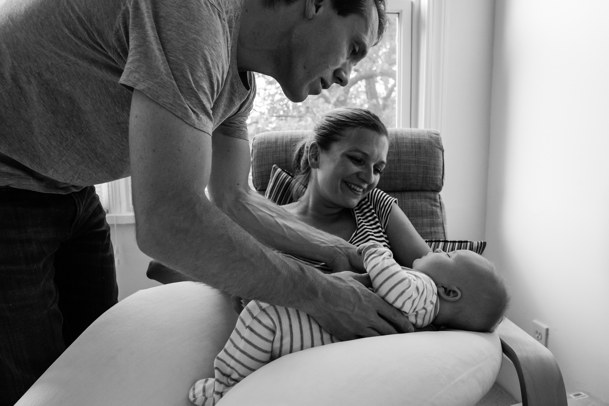Dad picking up sleeping baby from Mom by Washington, DC Family Photographer Nicole Sanchez