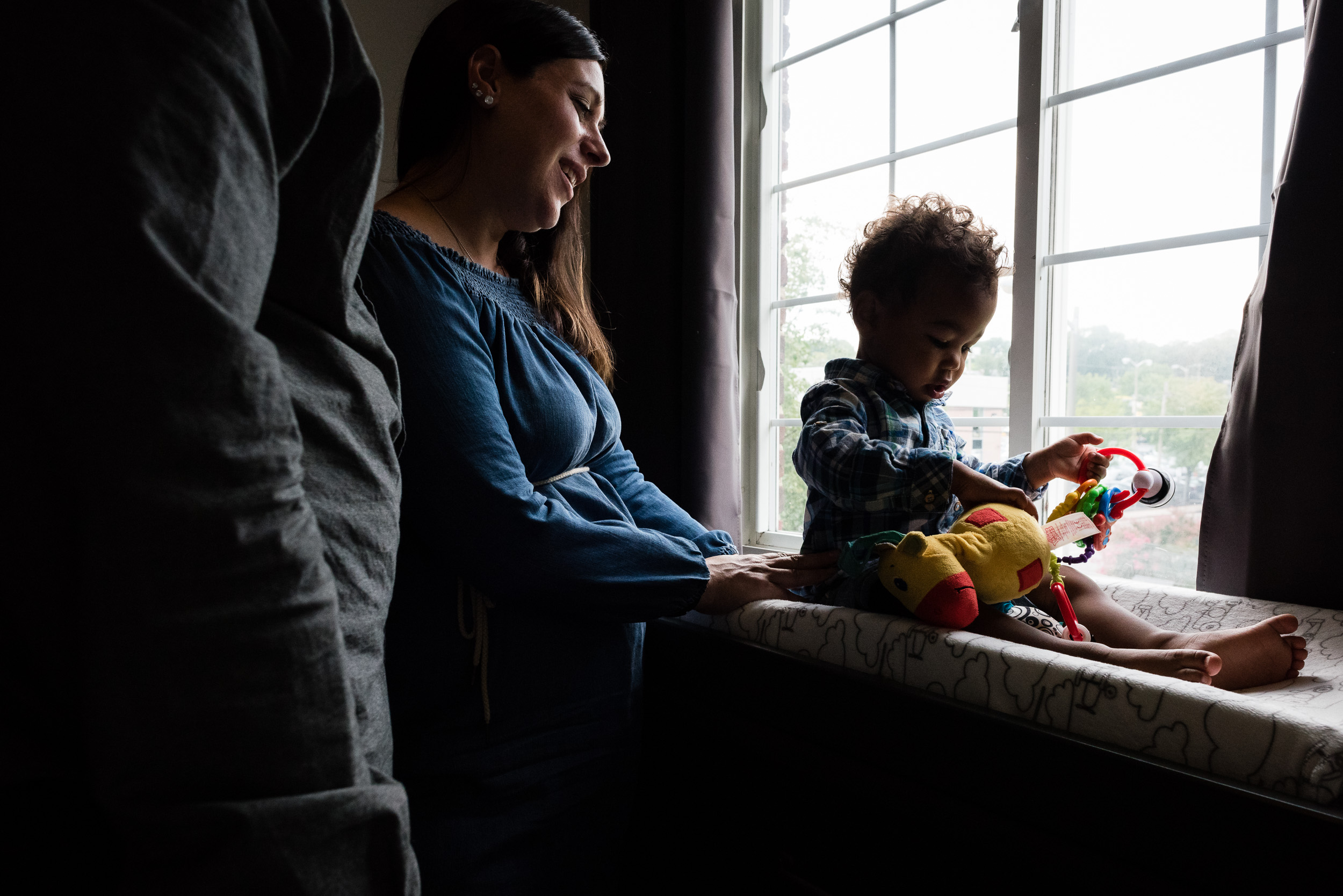 mom and dad playing with son in window at home session in alexandria va by family photographer nicole sanchez