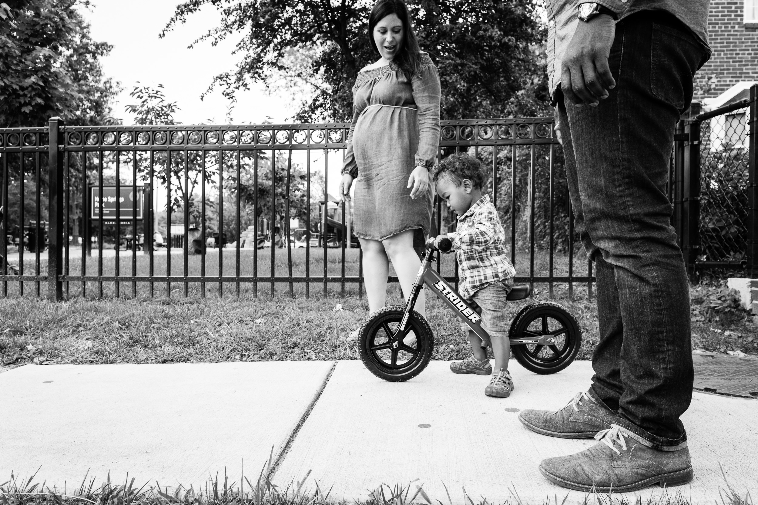 Parents walking with toddler on bike in Northern Virginia by Family Photographer Nicole Sanche