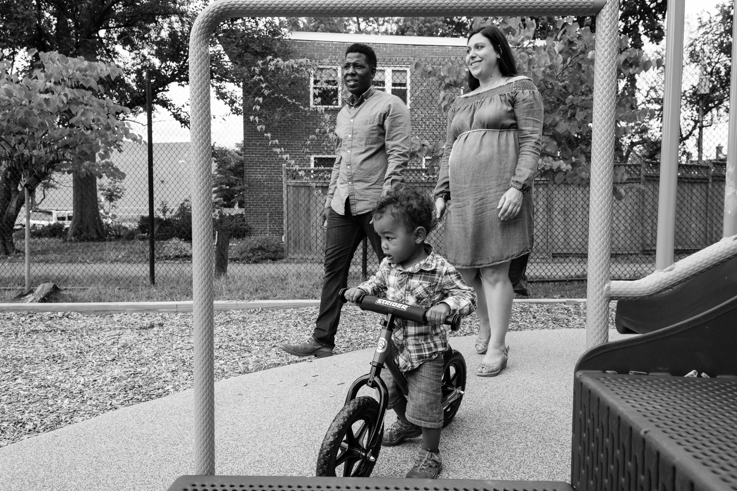 Toddler boy riding bike at playground with parents by Northern Virginia Family Photographer Nicole Sanchez