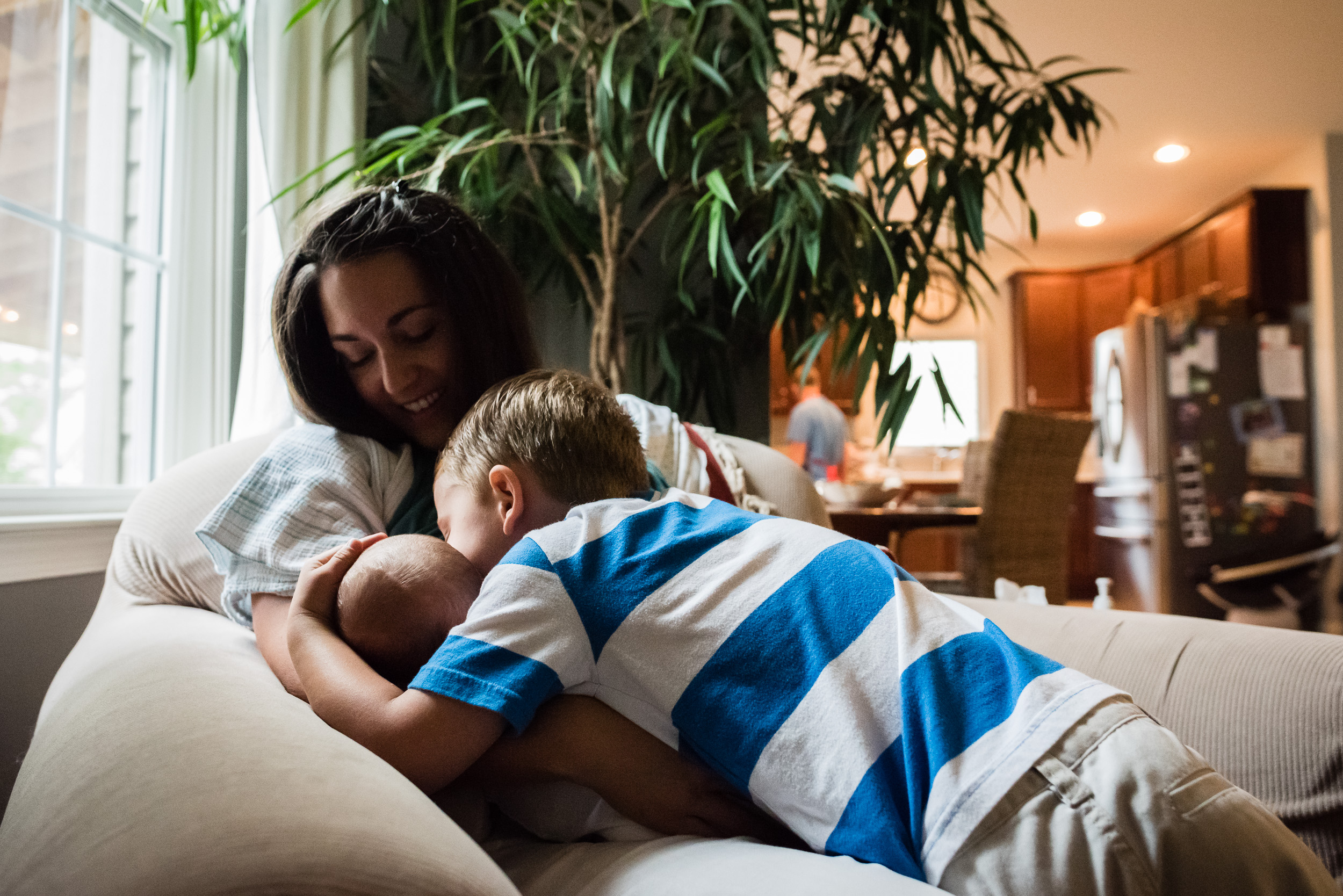 Big brother kissing newborn in at-home session in NOrthern Virginia by Family Photographer Nicole Sanchez