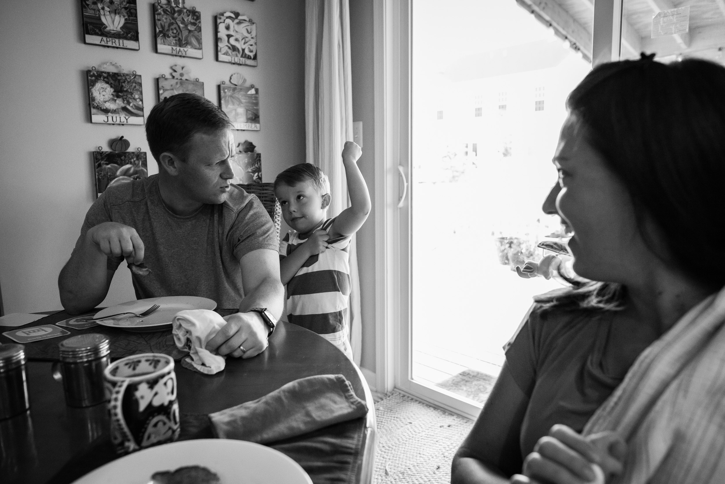 Boy showing off his muscle at family breakfast by Northern Virginia Photographer Nicole Sanchez