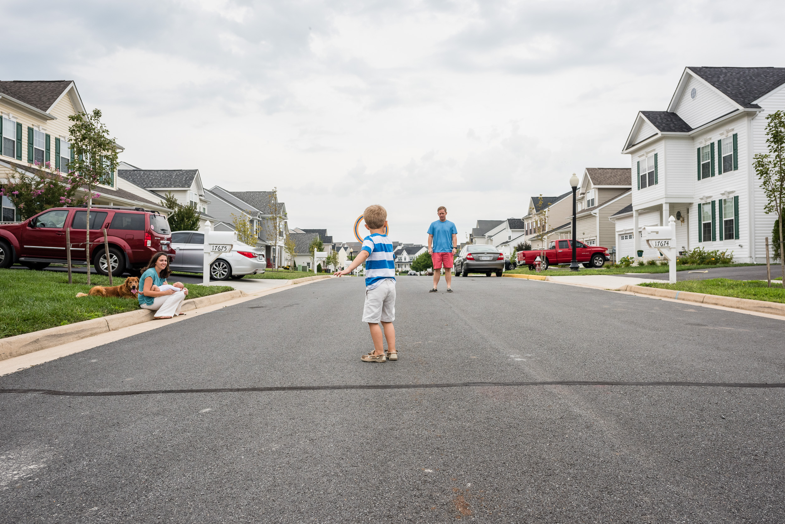 Father and son playing frisbee in street in Northern Virginia by Family Photographer Nicole Sanchez