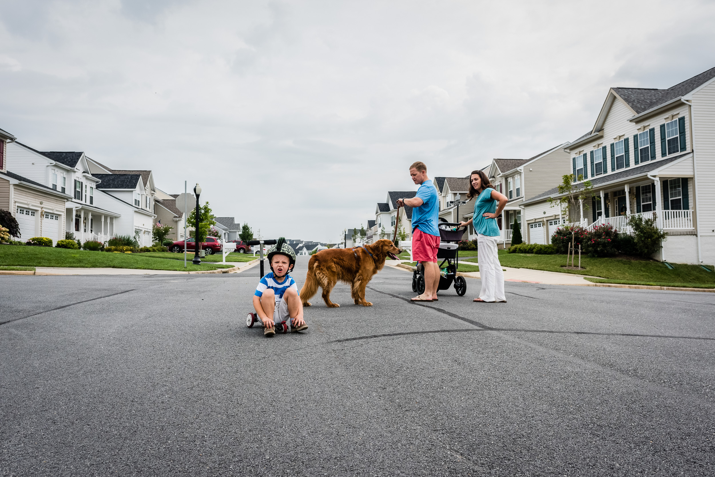 Parents waiting for boy Boy sitting in road on scooter by Northern Virginia Family Photographer Nicole Sanchez
